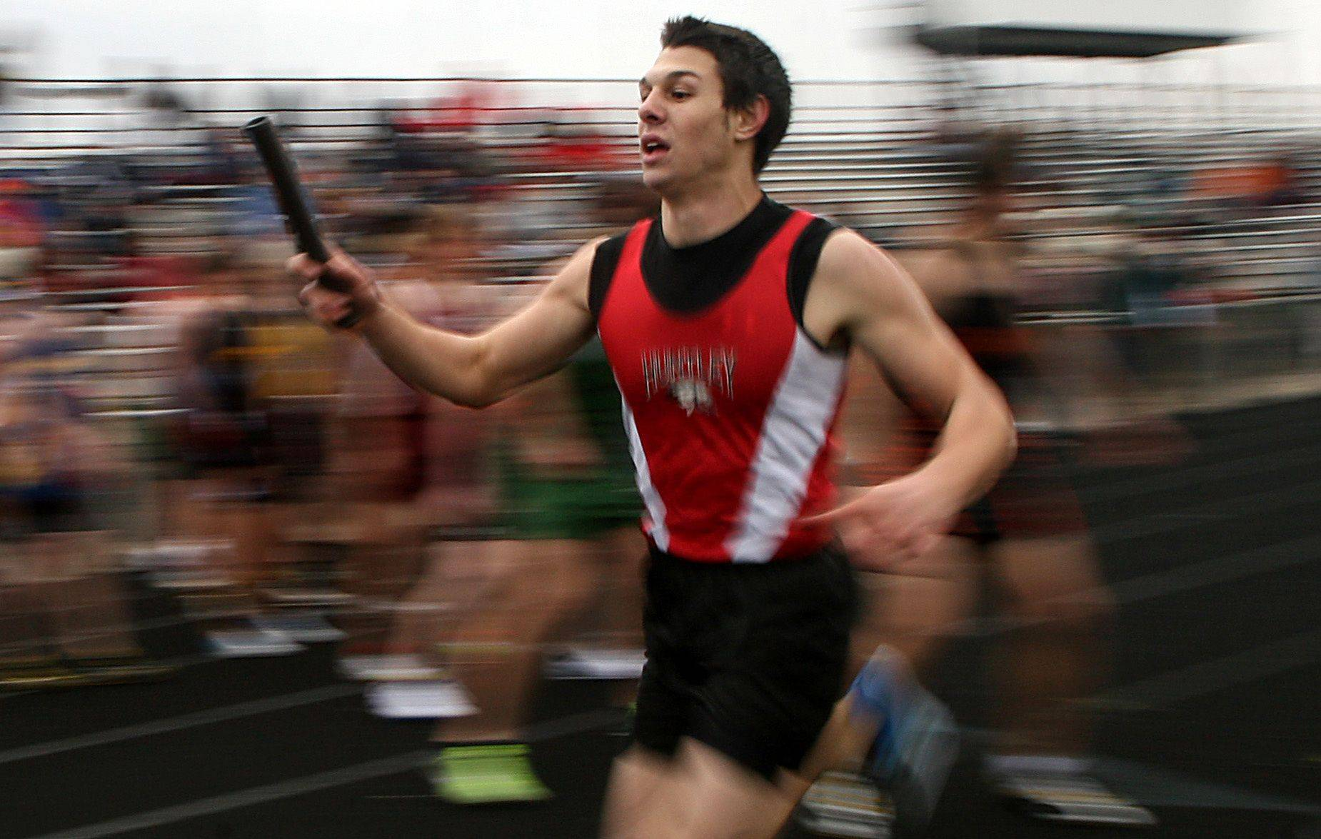 Huntley's Nate Kennedy looks to hand the baton off during the 3200-meter relay of the McHenry County Track Meet at Al Bohrer Field on the campus of Cary-Grove High School Thursday evening.