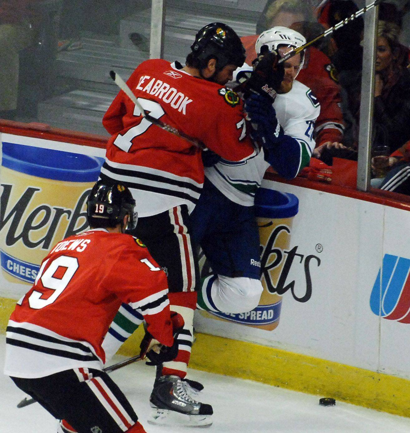 Rick West/rwest@dailyherald.com Chicago Blackhawks defenseman Brent Seabrook (7) checks Vancouver Canucks left wing Daniel Sedin (22) during Game Three of the NHL Western Conference Quarterfinals Sunday at the United Center in Chicago.