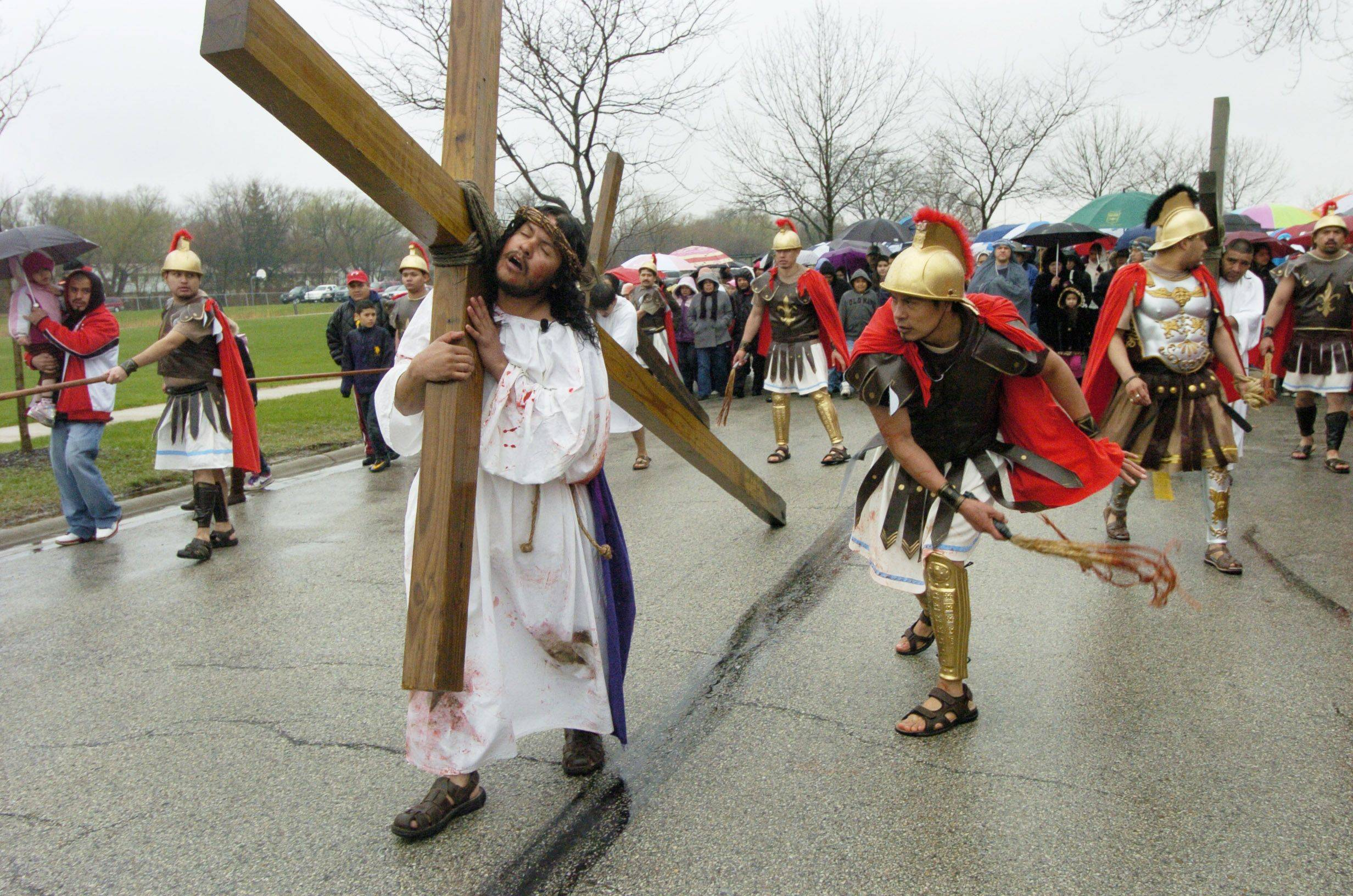 Jesus is whipped as he carries his cross during a Good Friday procession from St. Thomas Church in Palatine to Mission San Juan Diego in Arlington Heights.
