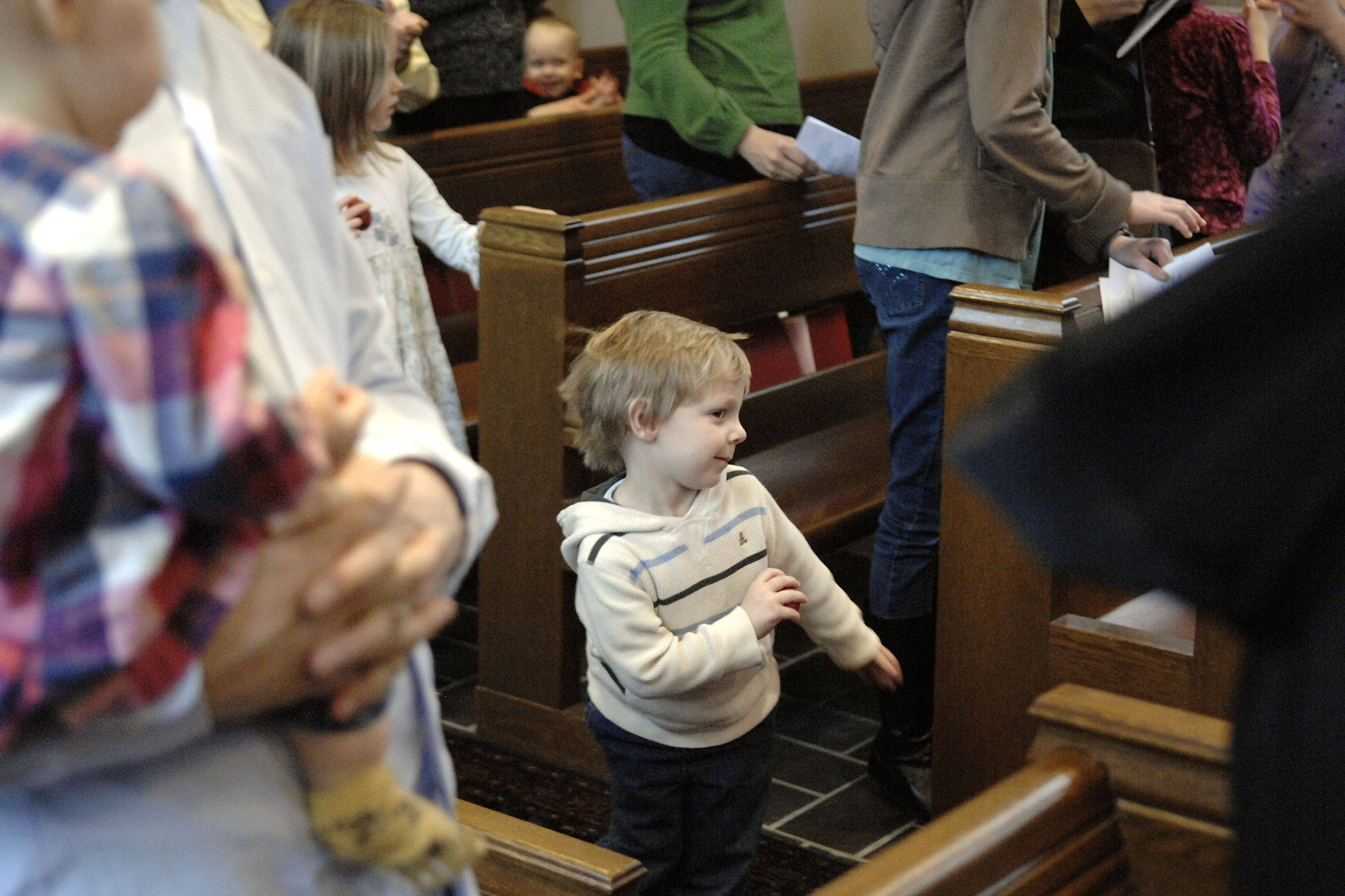 "Charlie Fredrickson, 3, of St. Charles dances in the aisle at Baker United Methodist Church in St. Charles while singing ""He's Got the Whole World in His Hands"" at the close of a Good Friday Family Worship service on April 22. The service used the Tomie DePaoloa children's book, ""Now One Foot, Now the Other"" to help children make sense of the Easter story."