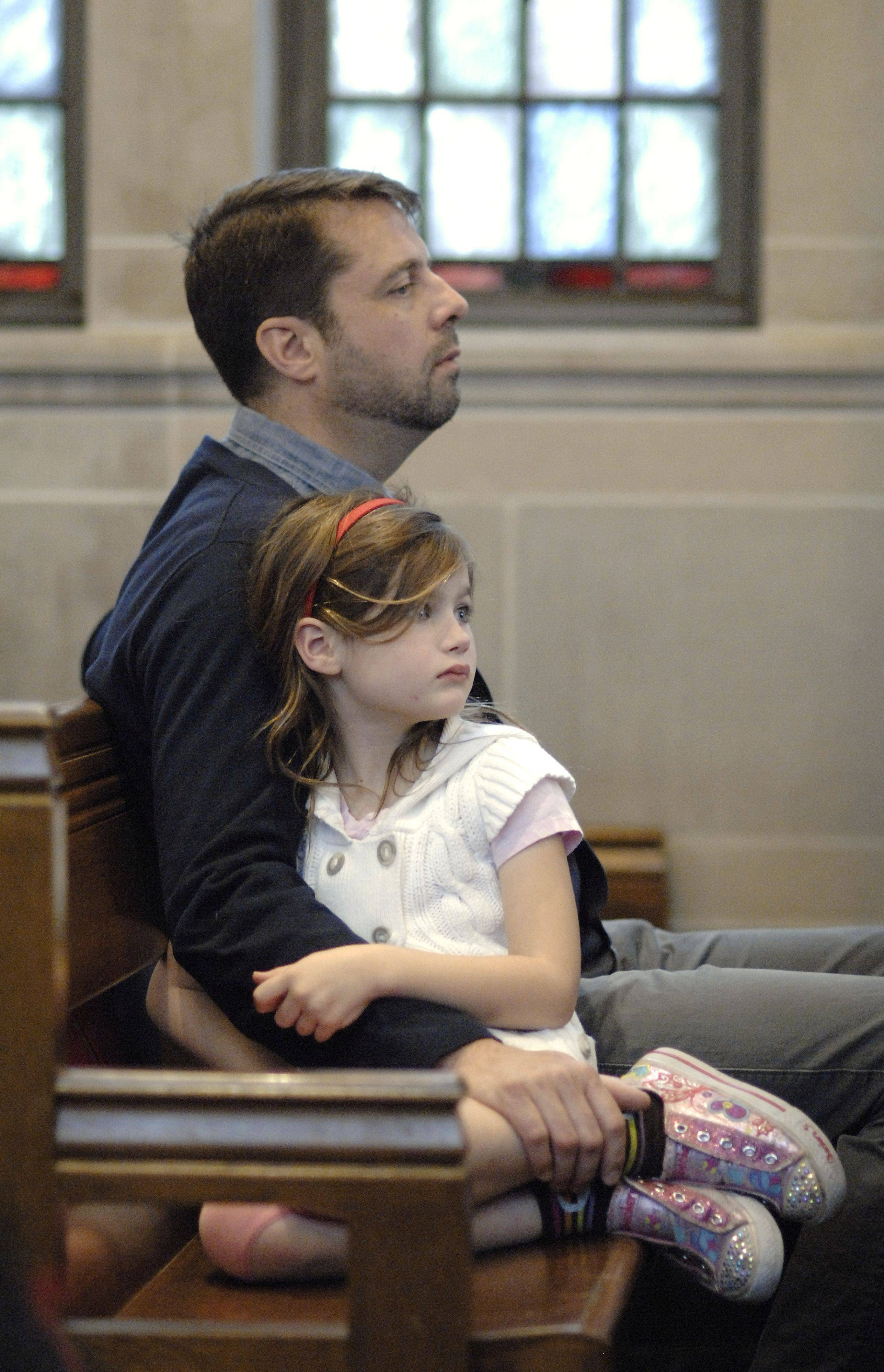 "Robert Powell of St. Charles and his daughter, Genevieve, 6, listen to Tomie DePaoloa children's book, ""Now One Foot, Now the Other"" read aloud in a Good Friday Family Worship service at Baker United Methodist to help children make sense of the Easter story on Friday, April 22."