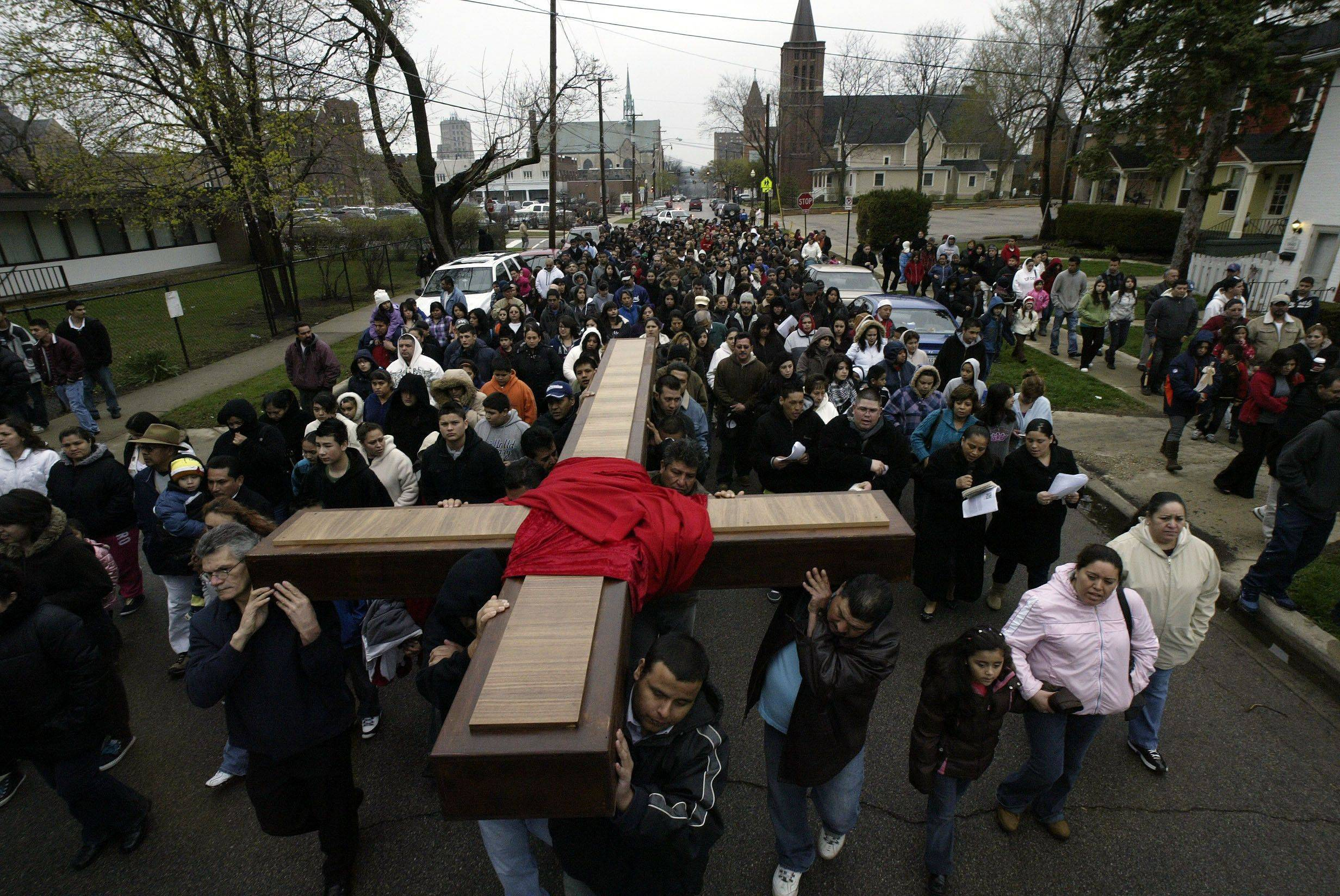 Reinaldo Sanchez of Elgin (front center) and others carry the cross Eastward along Division during St. Joseph's Passion Walk Good Friday, April 22, 2011 in Elgin.