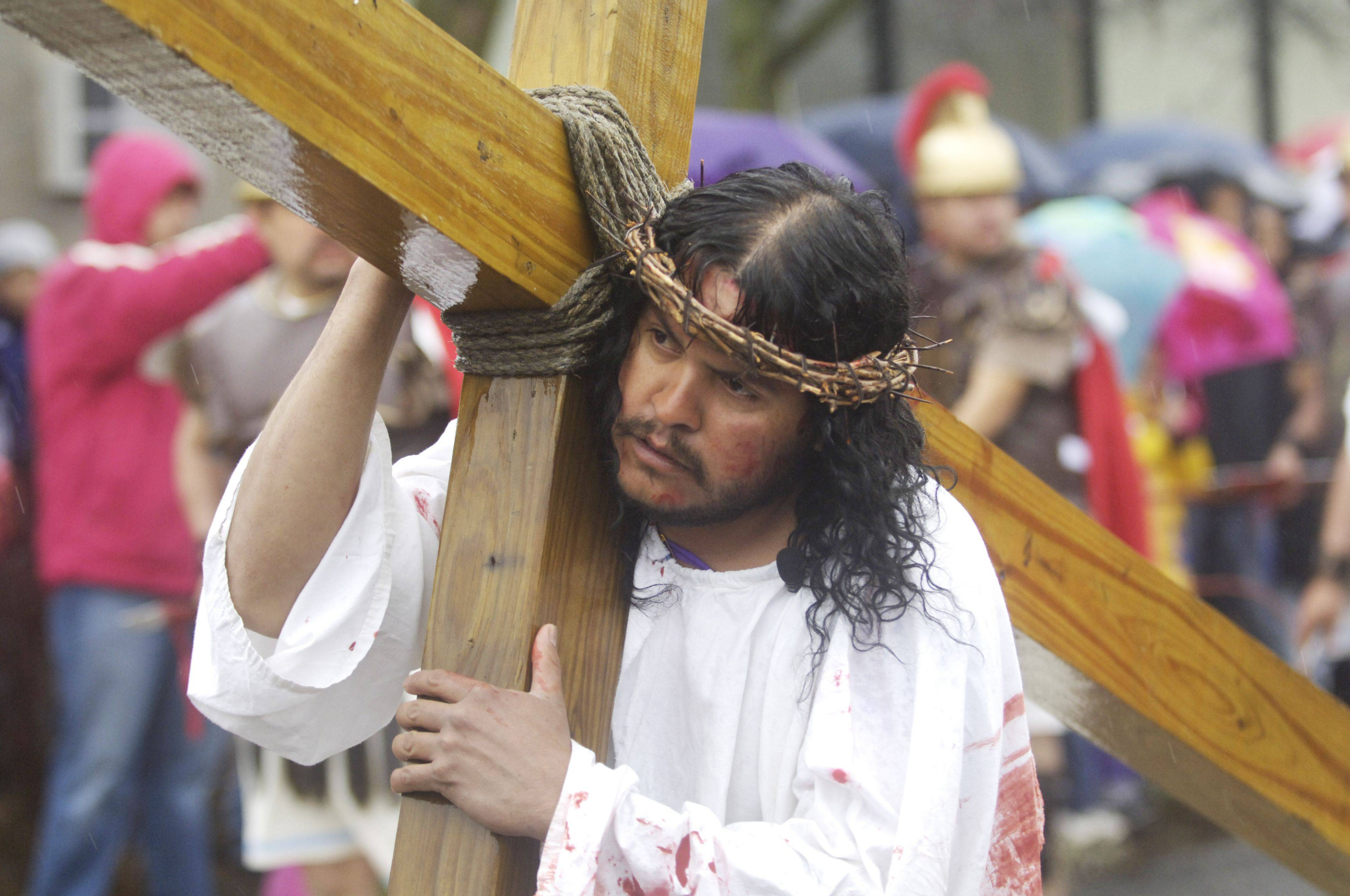 Jesus, played by Omar Parma, carries his cross during the Good Friday procession from St. Thomas Church to Mission San Juan Diego in Arlington Heights.