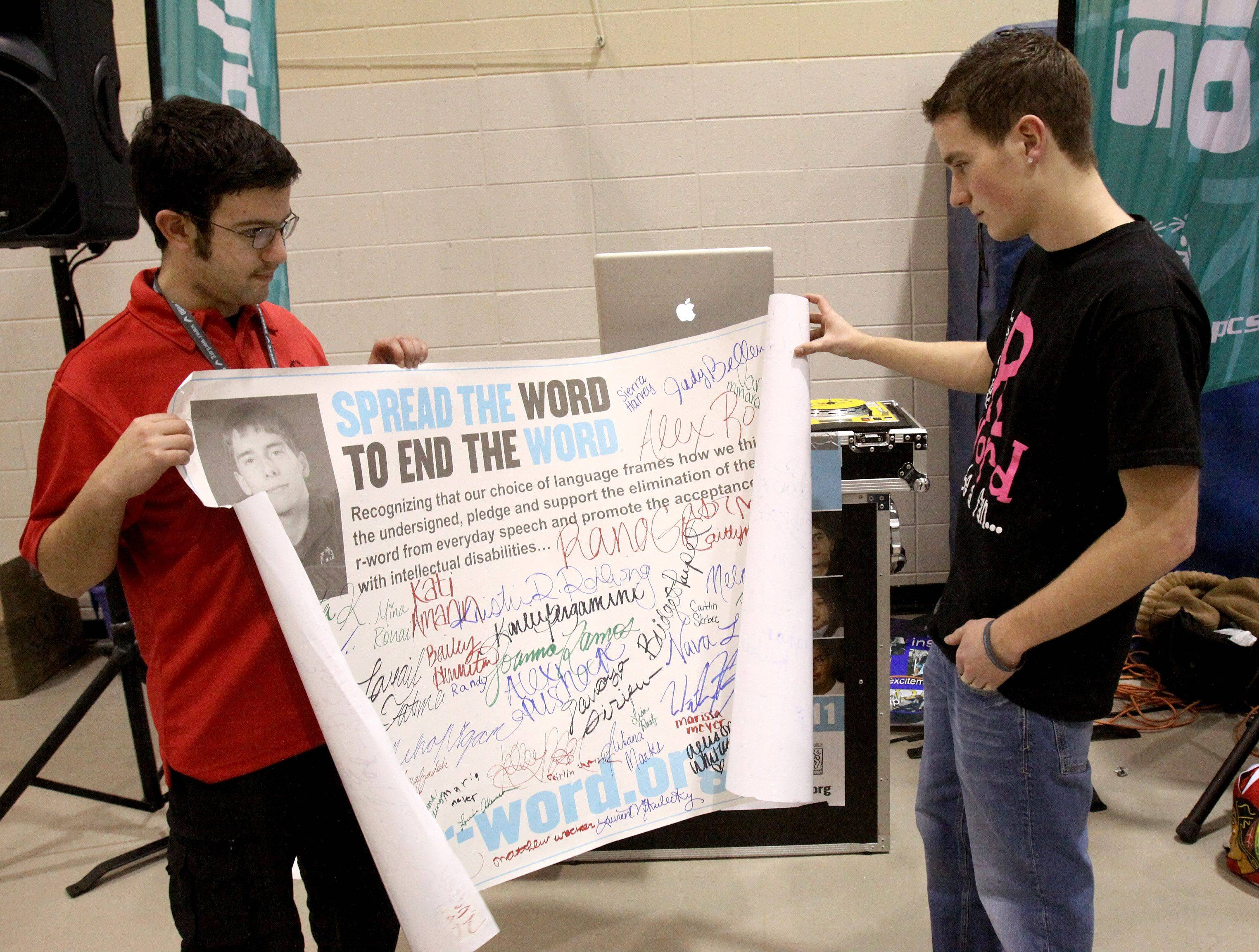 "Jordan Schubert, left, and classmate Andy Marsh check out a ""spread the word to end the word"" poster signed by participants at a recent Special Olympics swim meet in Naperville."