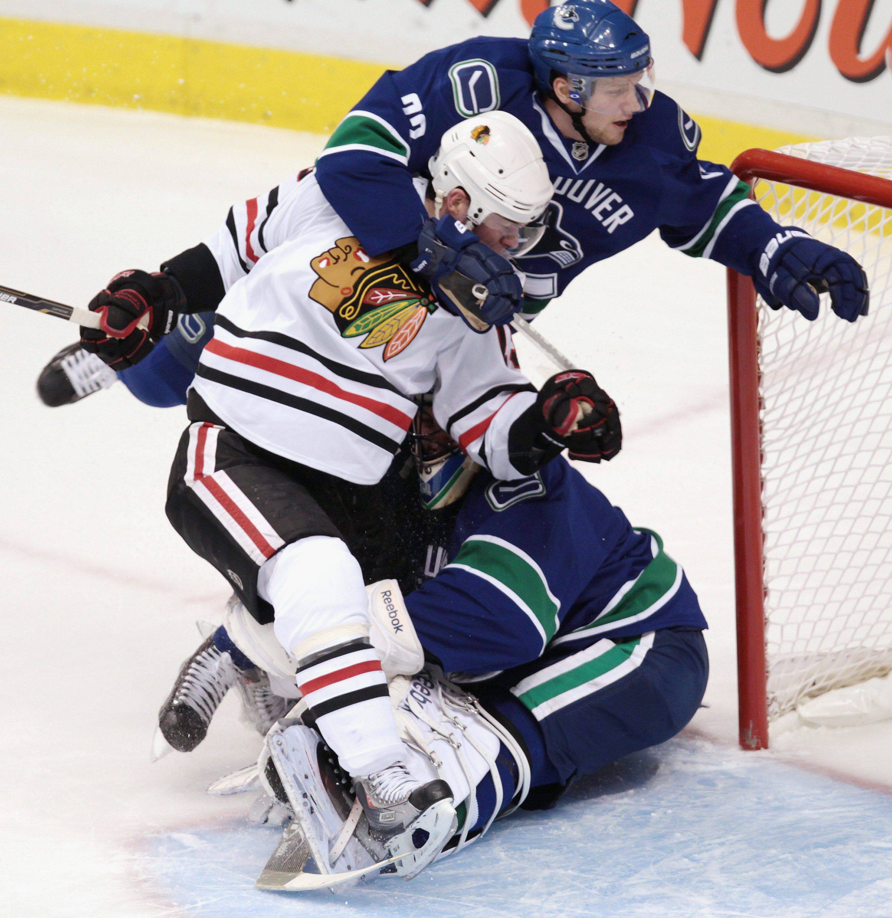 Jonathan Toews, left, and Vancouver Canucks' Alexander Edler, of Sweden, crash into Canucks goalie Roberto Luongo during the first period of Game 5 of an NHL hockey Stanley Cup playoffs first-round series in Vancouver, British Columbia, on Thursday April 21, 2011.