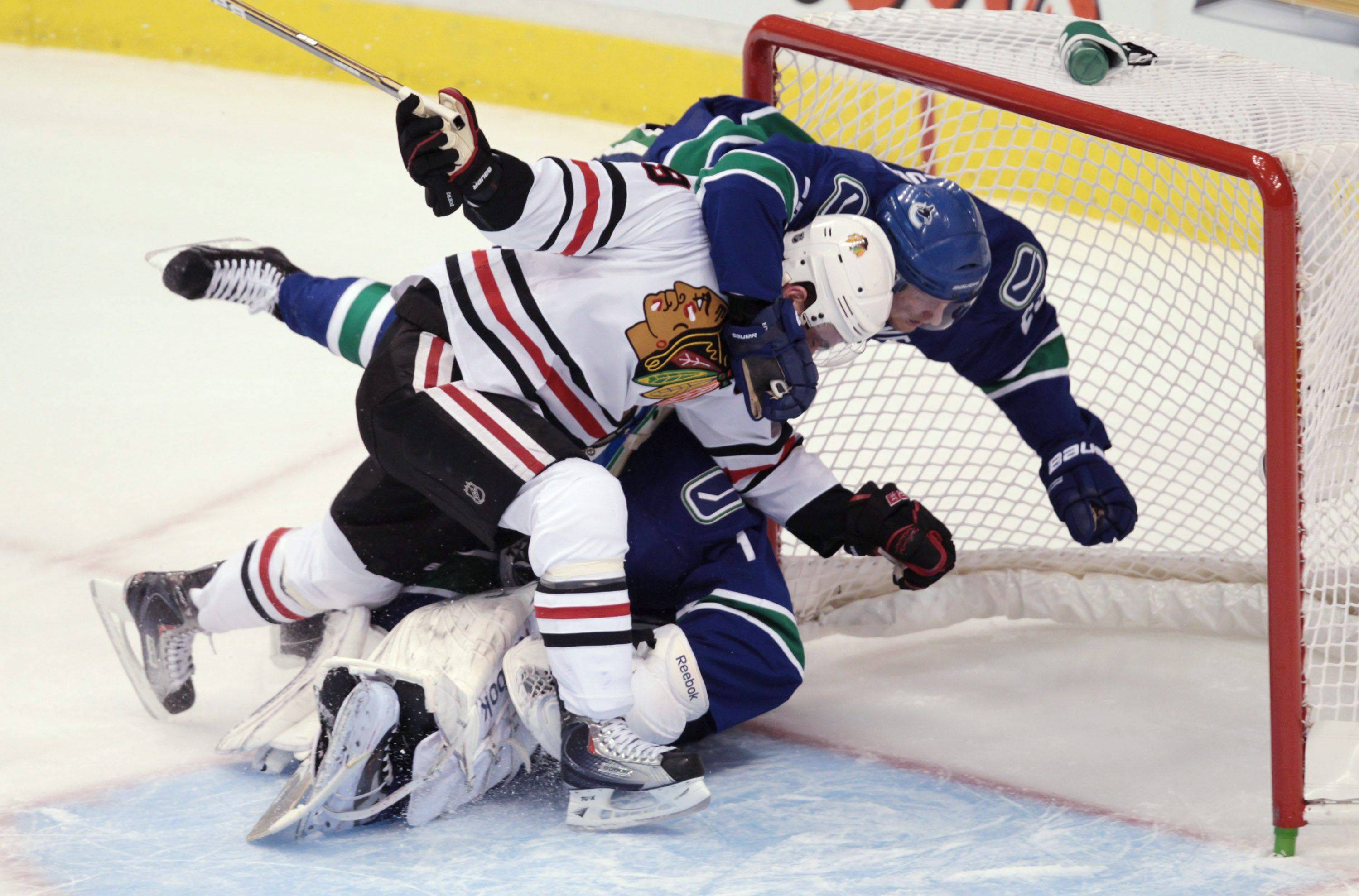 Jonathan Toews and the Canucks' Alexander Edler crash into Canucks goalie Roberto Luongo during the first period of Game 5.