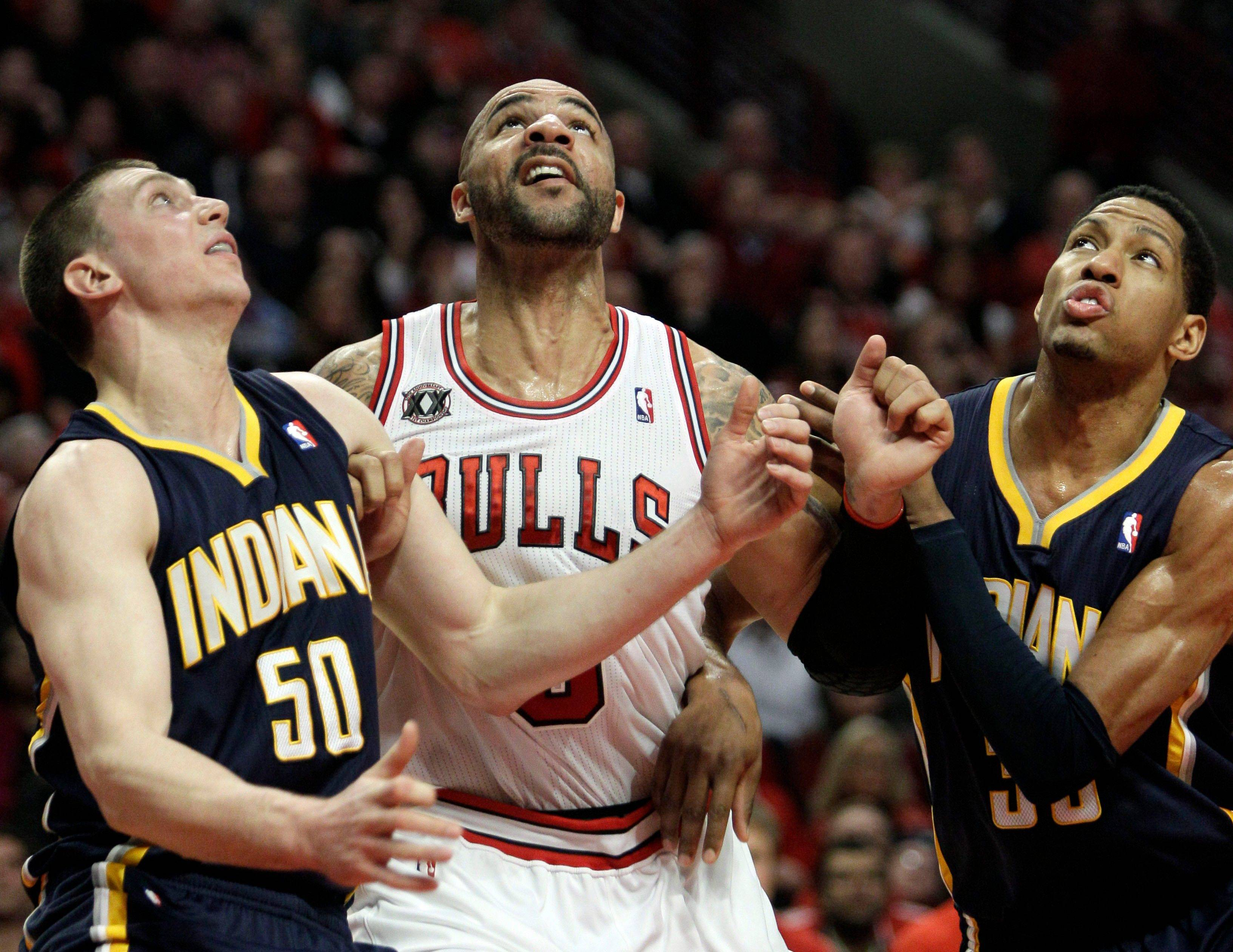 Carlos Boozer, center, looks up as he battles for a rebound against Indiana Pacers' Tyler Hansbrough, left, and Danny Granger during the quarter in Game 2 of a first-round NBA playoff basketball series in Chicago, Monday, April 18, 2011. The Bulls won 96-90.