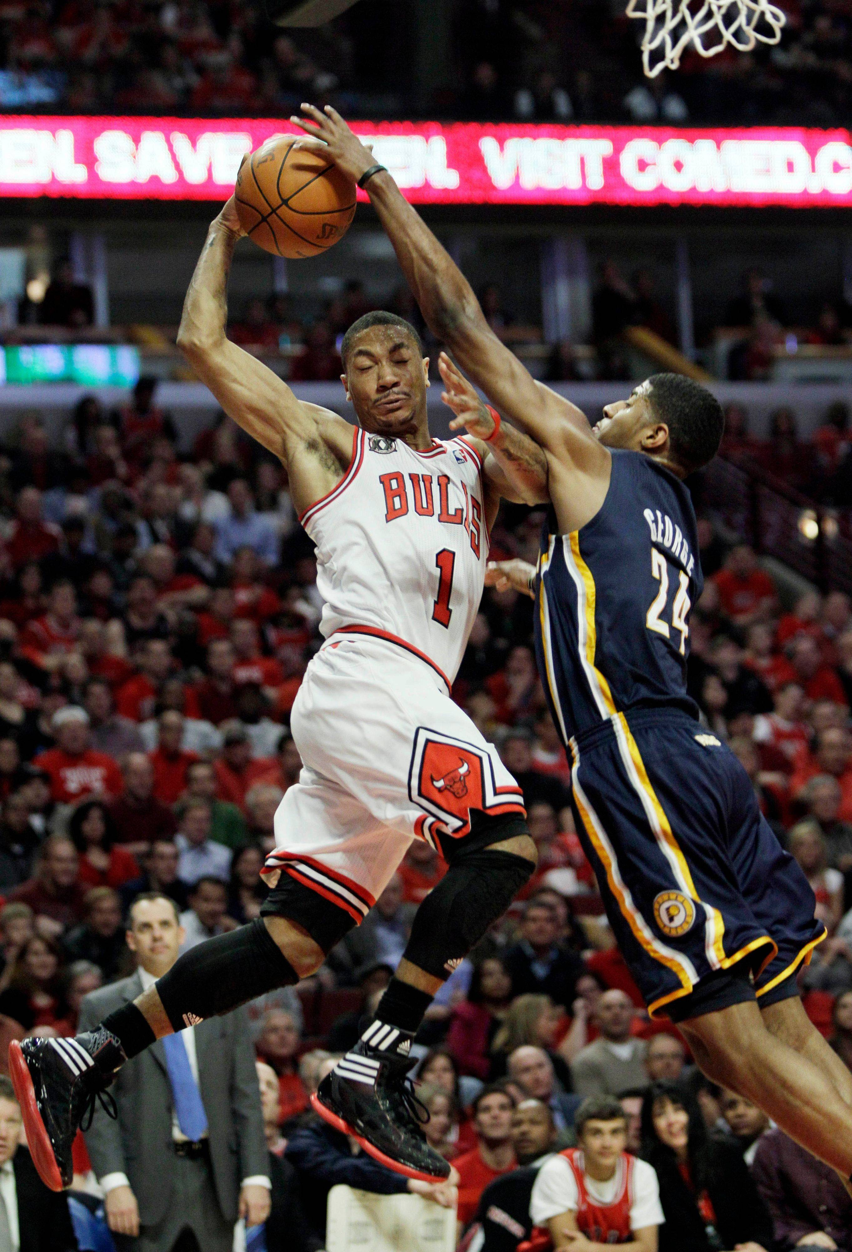 Derrick Rose, left, drives to the basket against the Indiana Pacers' Paul George during the third quarter in Game 2. The Bulls won the game 96-90.
