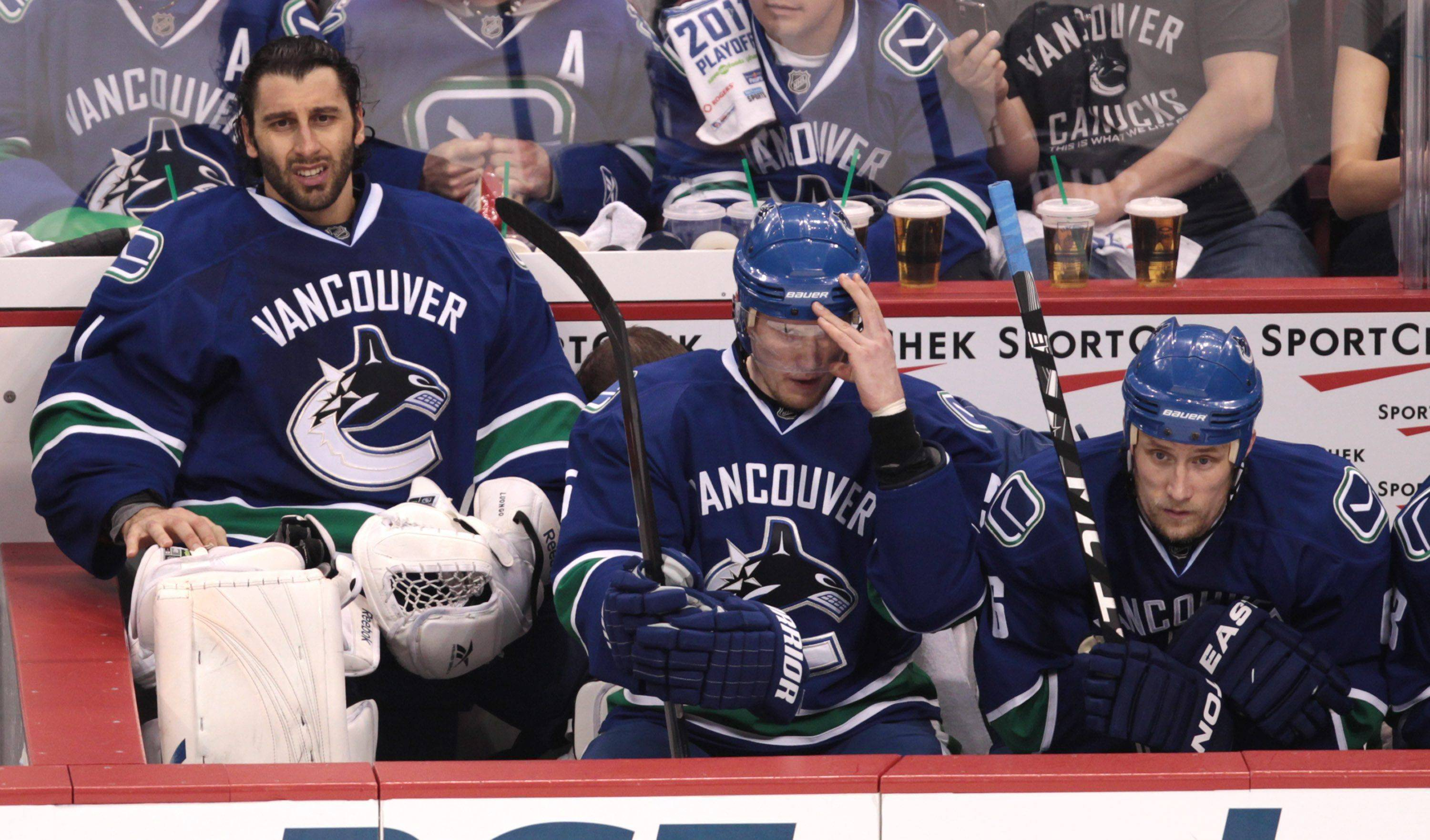 Vancouver Canucks goalie Roberto Luongo, left, sits on the bench after being replaced by backup goalie Cory Schneider, as Christian Ehrhoff, center, and Sami Salo sit next to him during the second period against the Blackhawks in Game 5 of their NHL playoffs series Thursday.