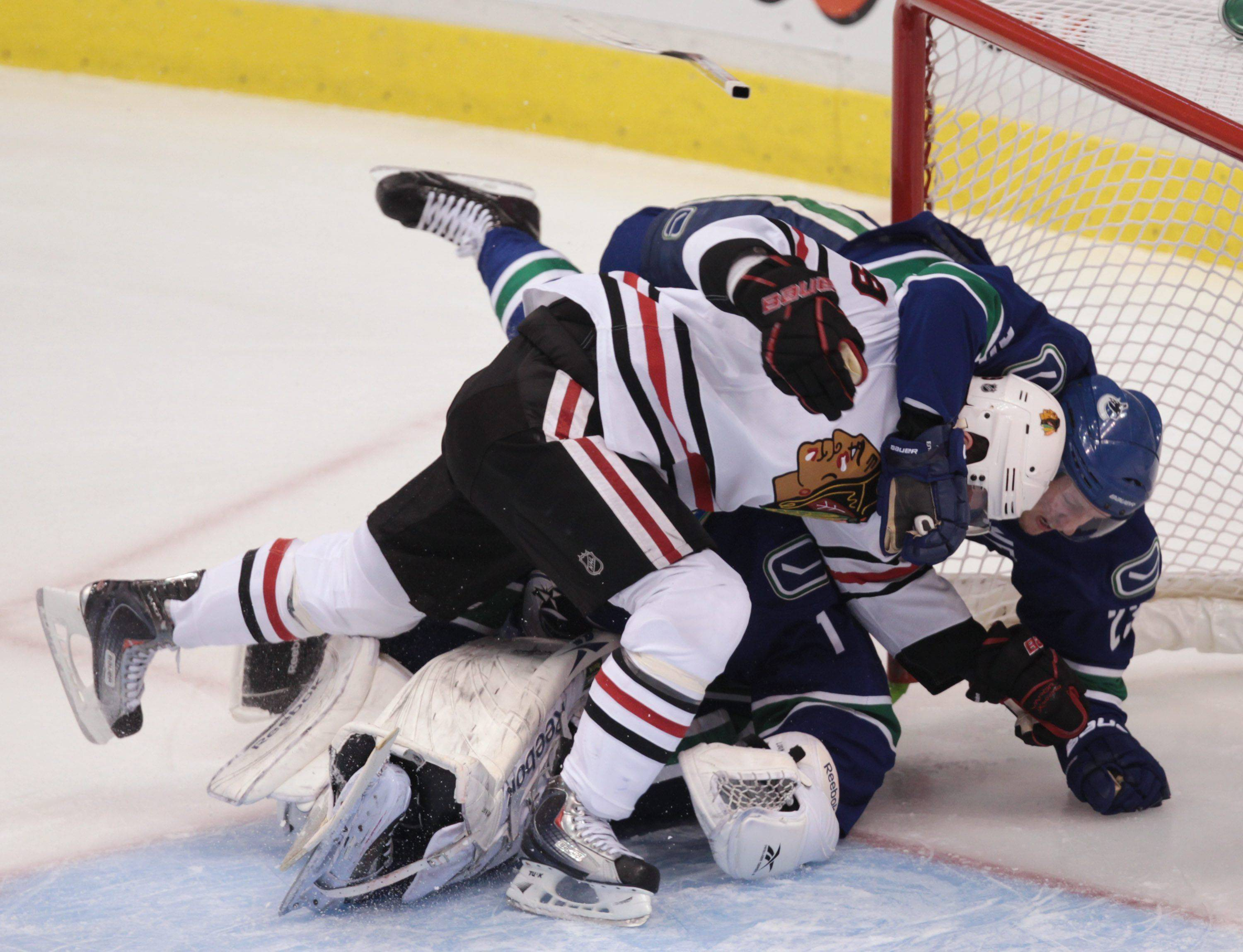 Chicago Blackhawks' Jonathan Toews, left, and Vancouver Canucks' Alexander Edler crash into Canucks' goalie Roberto Luongo, back, during the first period.