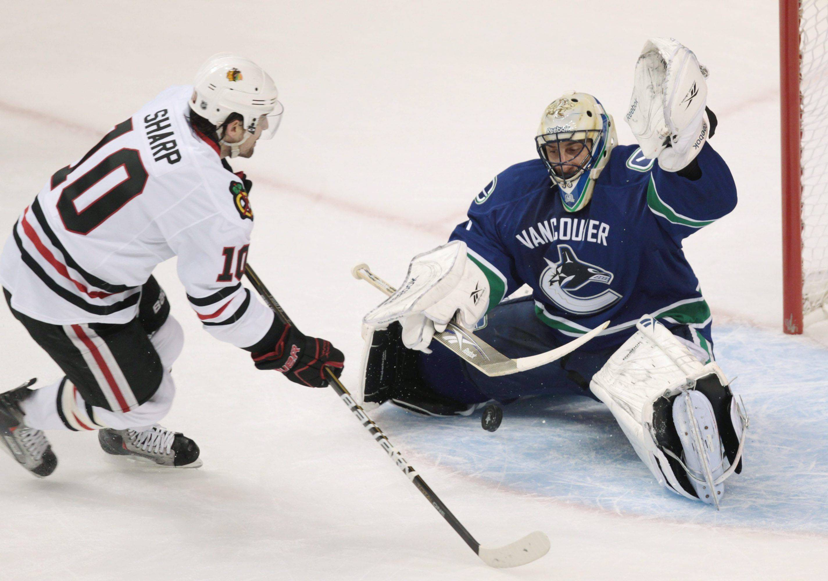 Chicago Blackhawks' Patrick Sharp, left, has his shot stopped by Vancouver Canucks' Roberto Luongo during the first period.
