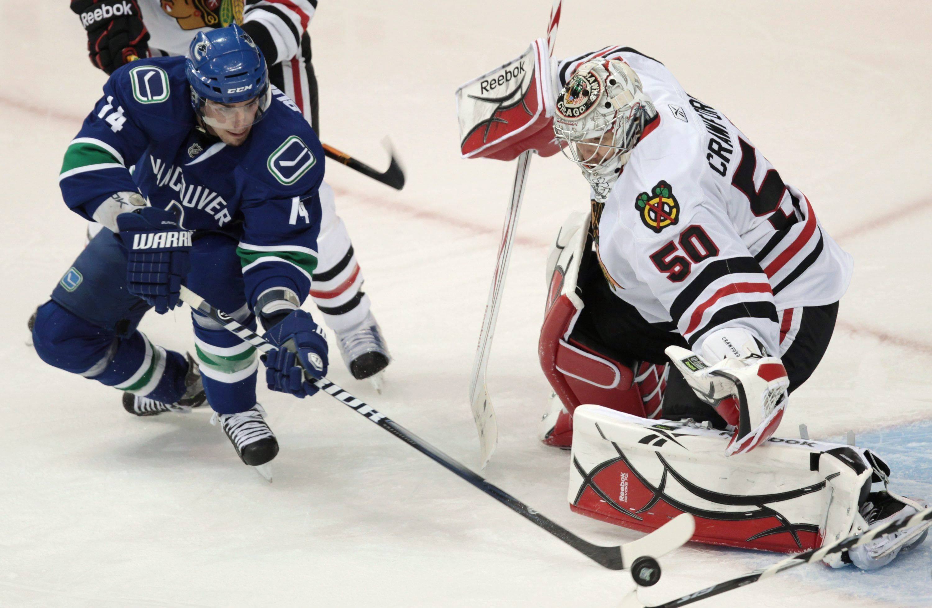 Vancouver Canucks' Alex Burrows, left, is stopped by Chicago Blackhawks' Corey Crawford during the second period.