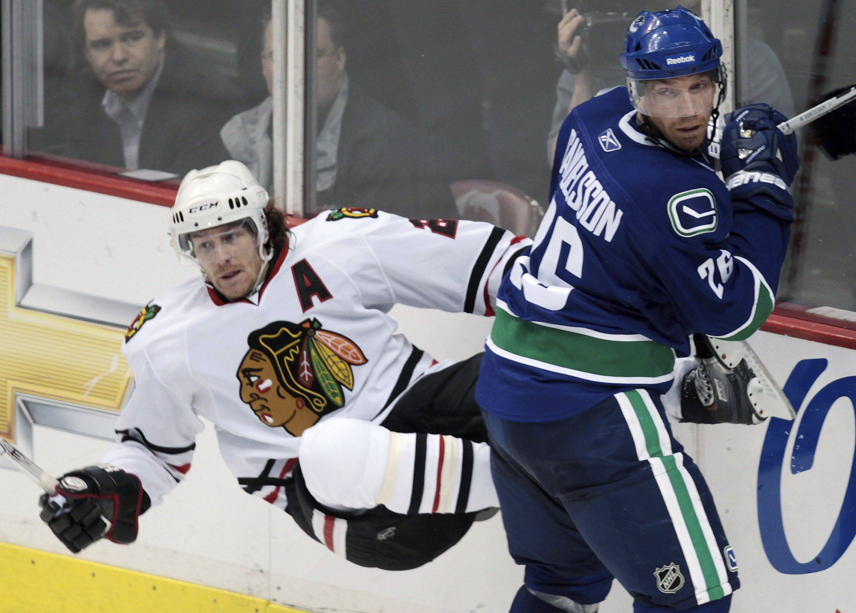 Vancouver Canucks' Mikael Samuelsson, right, checks Chicago Blackhawks' Duncan Keith during the second period.