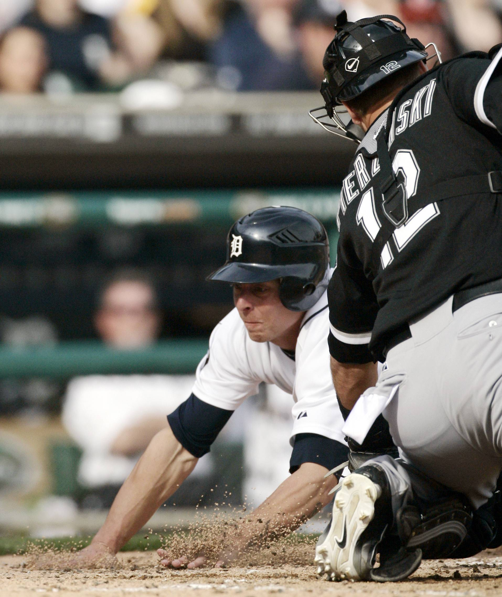 The Detroit Tigers' Brandon Inge dives past A.J. Pierzynski to score from third base on a single by Magglio Ordonez in the fifth inning on Saturday.