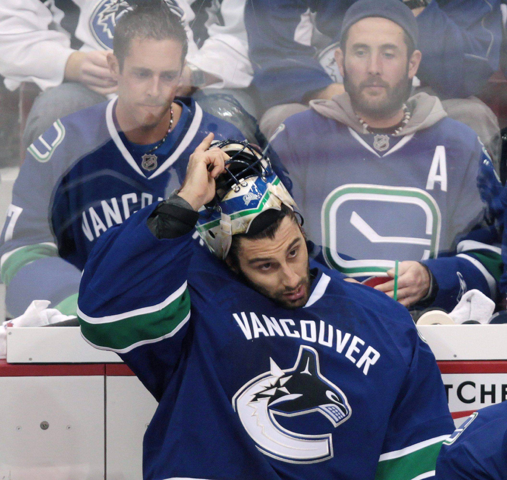 Vancouver's Roberto Luongo takes off his mask on the bench after being replaced by backup goalie Cory Schneider during the second period of Game 5 of the Stanley Cup playoffs first-round series against the Blackhawks.