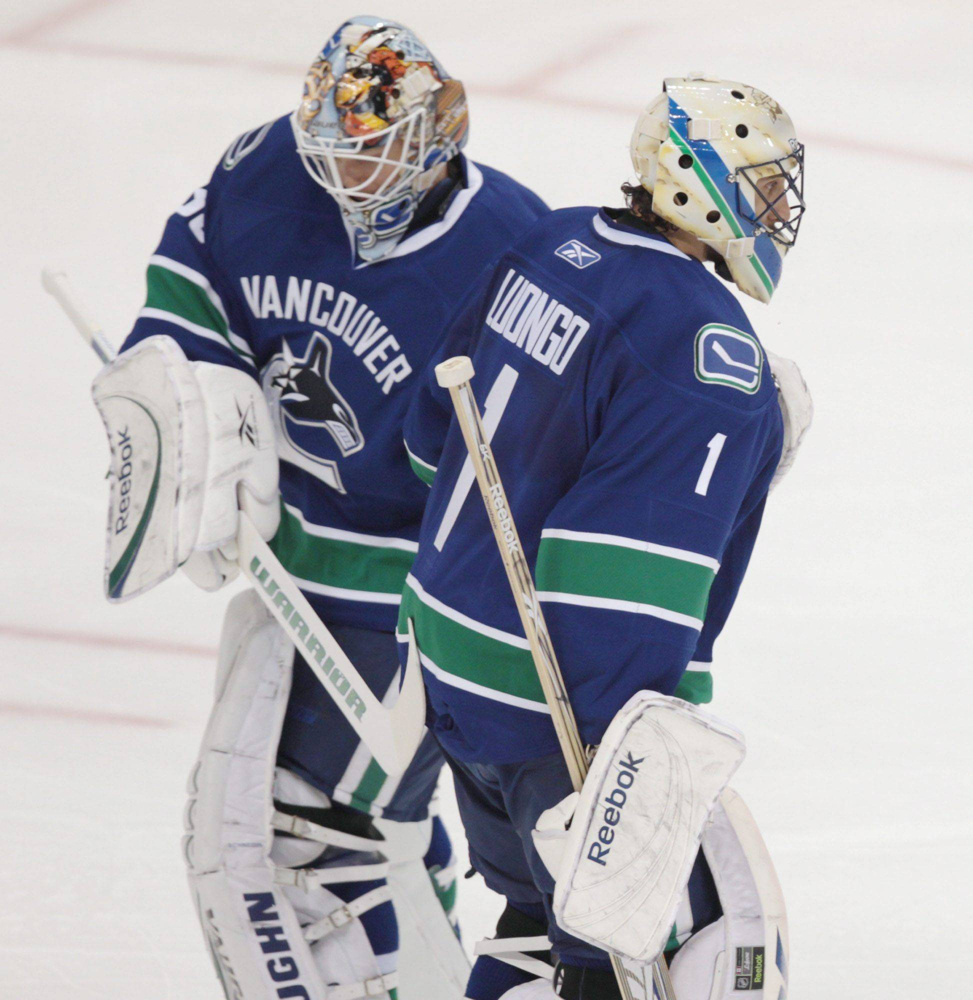 Vancouver Canucks' Roberto Luongo, right, leaves the ice and is replaced by Cory Schneider, left, during the second period against the Chicago Blackhawks in Game 5 of an NHL hockey Stanley Cup playoffs first-round series in Vancouver, British Columbia, on Thursday, April 21, 2011.