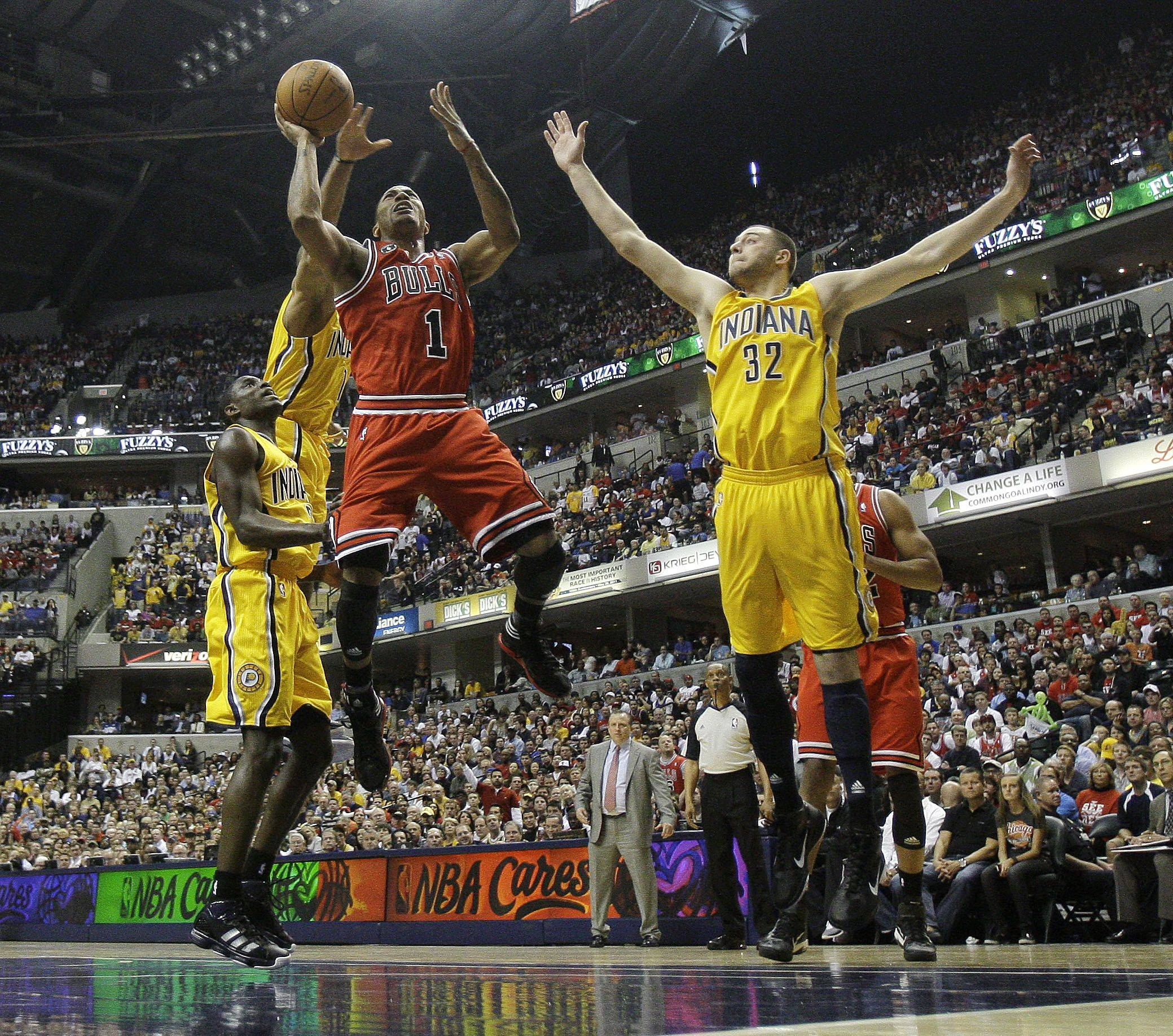 Chicago Bulls' Derrick Rose (1) puts up a shot against Indiana Pacers' Darren Collison (2) and Josh McRoberts (32) during the first half of Game 4 of a first-round NBA basketball series in Indianapolis, Saturday, April 23, 2011.