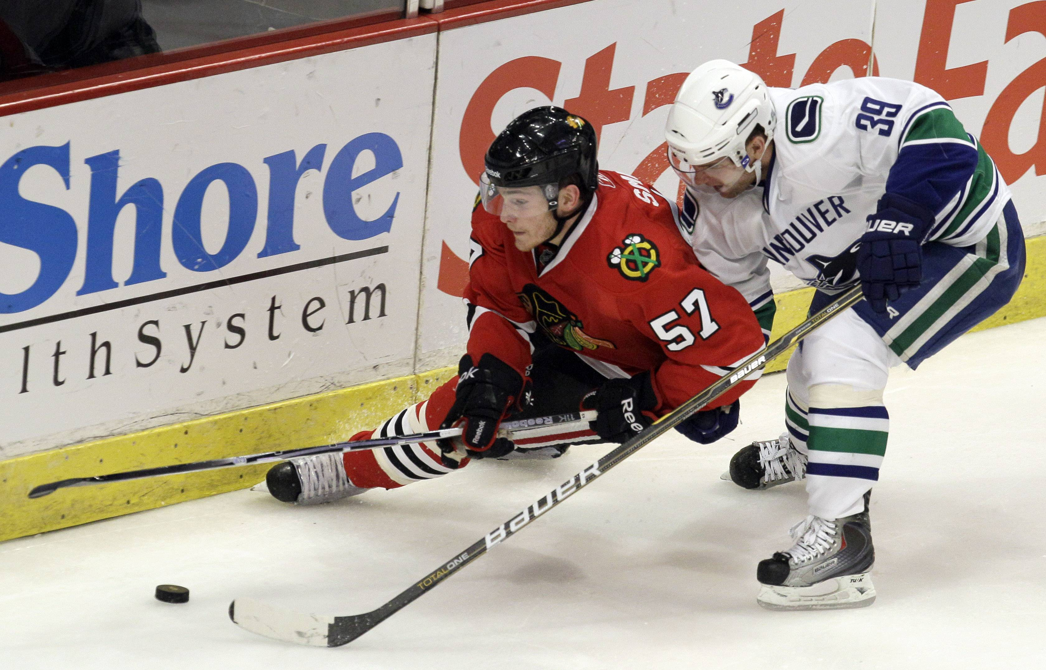 Chicago Blackhawks right wing Ben Smith (57) and Vancouver Canucks center Cody Hodgson (39) fight for the puck Sunday during the third period at the United Center. Smith scored on a rebound during overtime, allowing the Hawks to force a seventh game in the opening-round series.