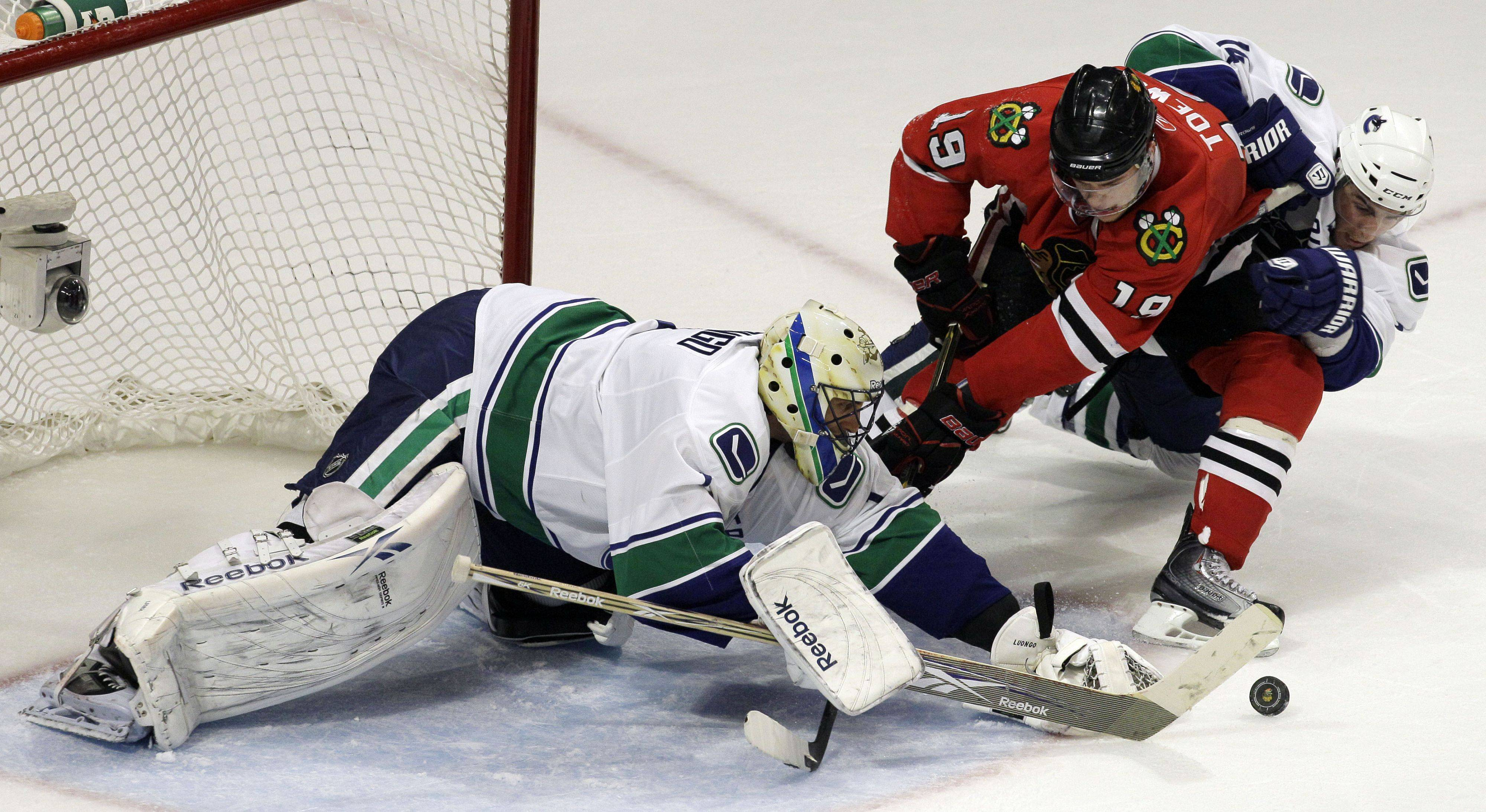 Vancouver Canucks goalie Roberto Luongo makes a save as Chicago Blackhawks center Jonathan Toews (19) and Vancouver Canucks left wing Alex Burrows battle for the puck during the third period.