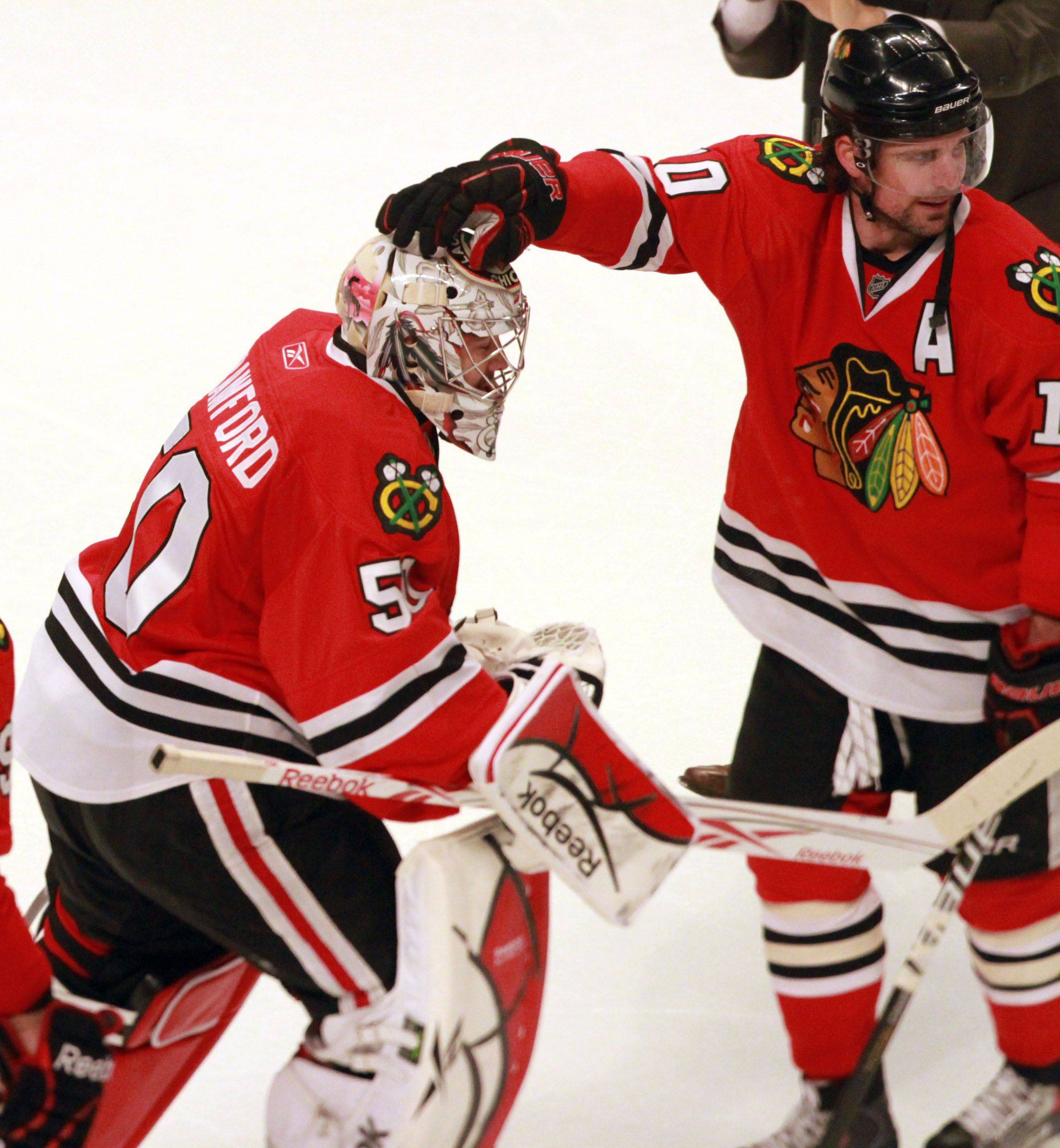 Chicago Blackhawks goalie Corey Crawford gets a hand from Patrick Sharp after 4-3 win in overtime against the Vancouver Canucks in game 6 of the Stanley Cup quarterfinals at the United Center in Chicago on Sunday.