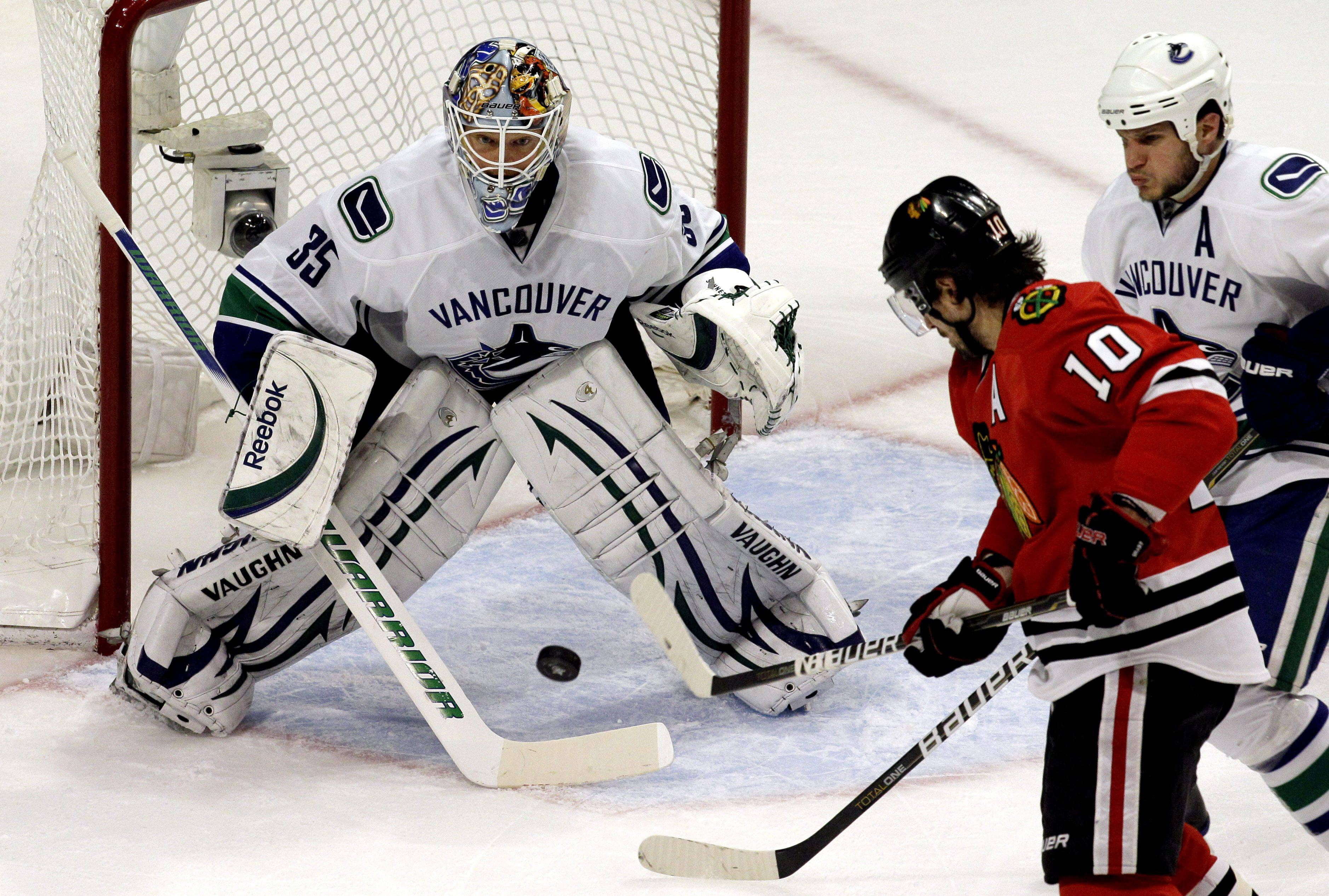 Vancouver Canucks goalie Cory Schneider stops a shot by Chicago Blackhawks center Patrick Sharp (10) during the first period. At right is Vancouver Canucks defenseman Kevin Bieksa.