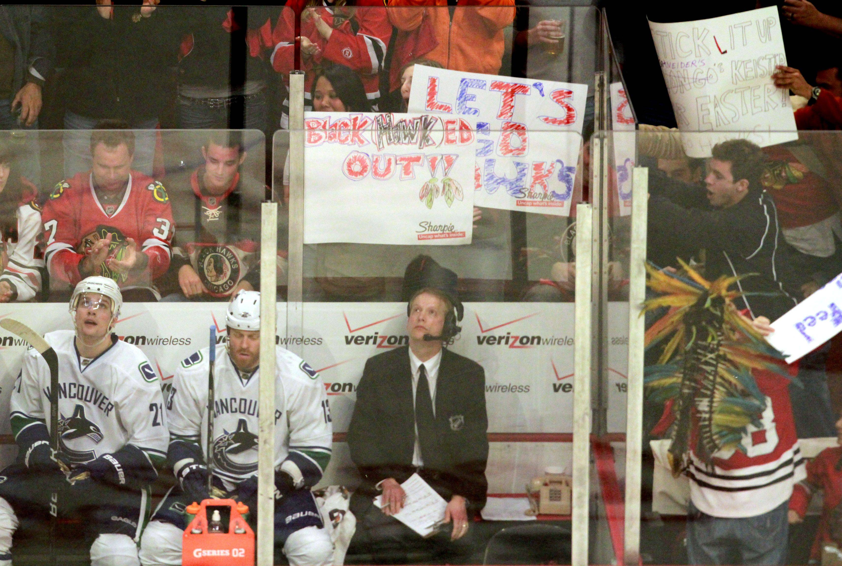 Chicago Blackhawks fans hold up signs with two Vancouver Canucks players in the penalty box in game 6 of the Stanley Cup quarterfinals at the United Center in Chicago on Sunday.