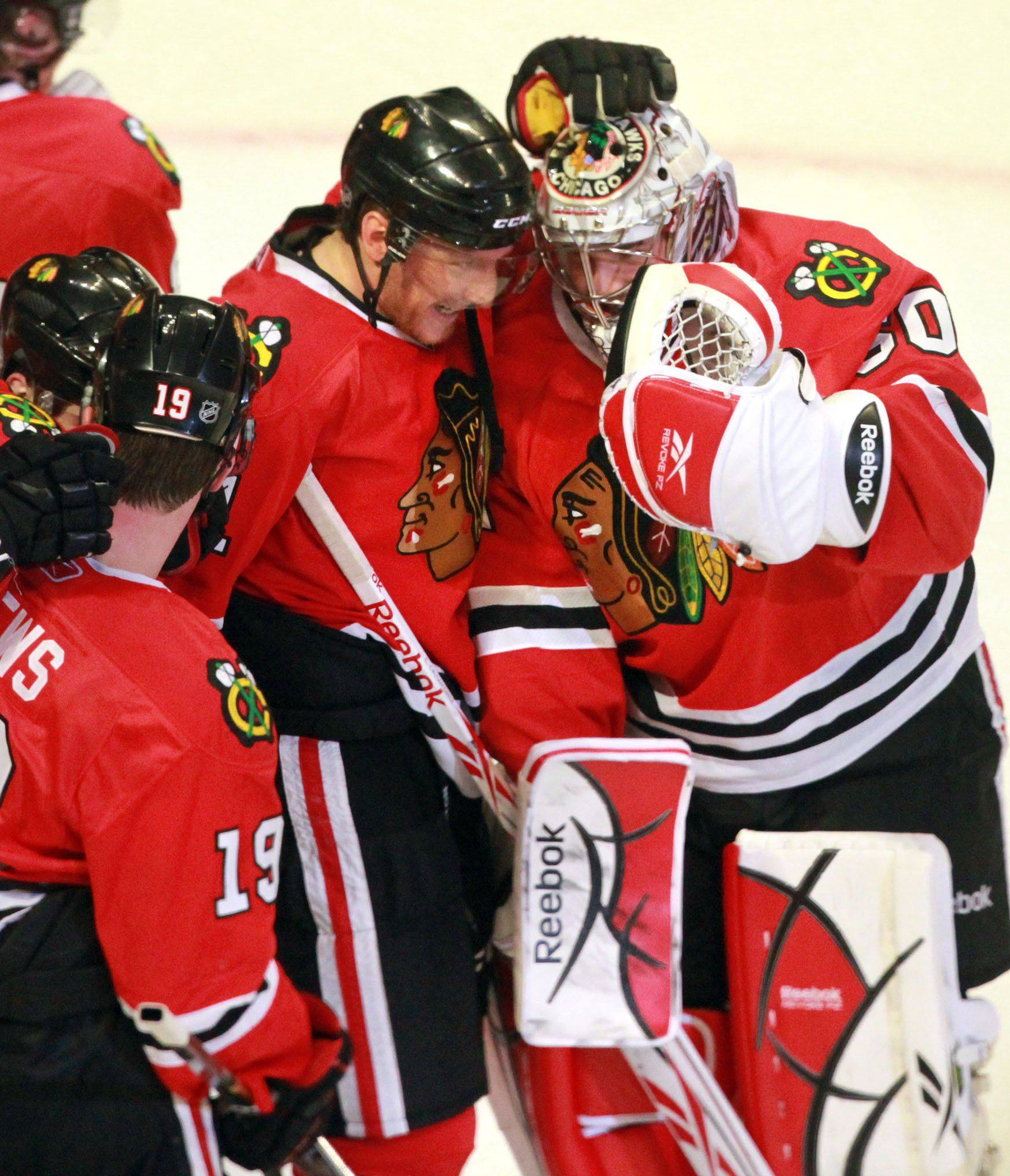 Blackhawks goalie Corey Crawford gets a hand from Marian Hossa after Sunday's 4-3 win in overtime against the Vancouver Canucks in Game 6 at the United Center.