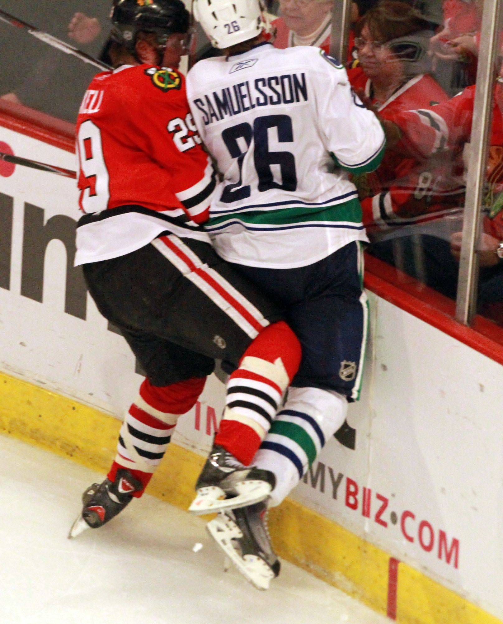 The Hawks' Bryan Bickell gets hit near his right wrist by the Canucks' Mikael Samuelsson in Game 6 Sunday night.