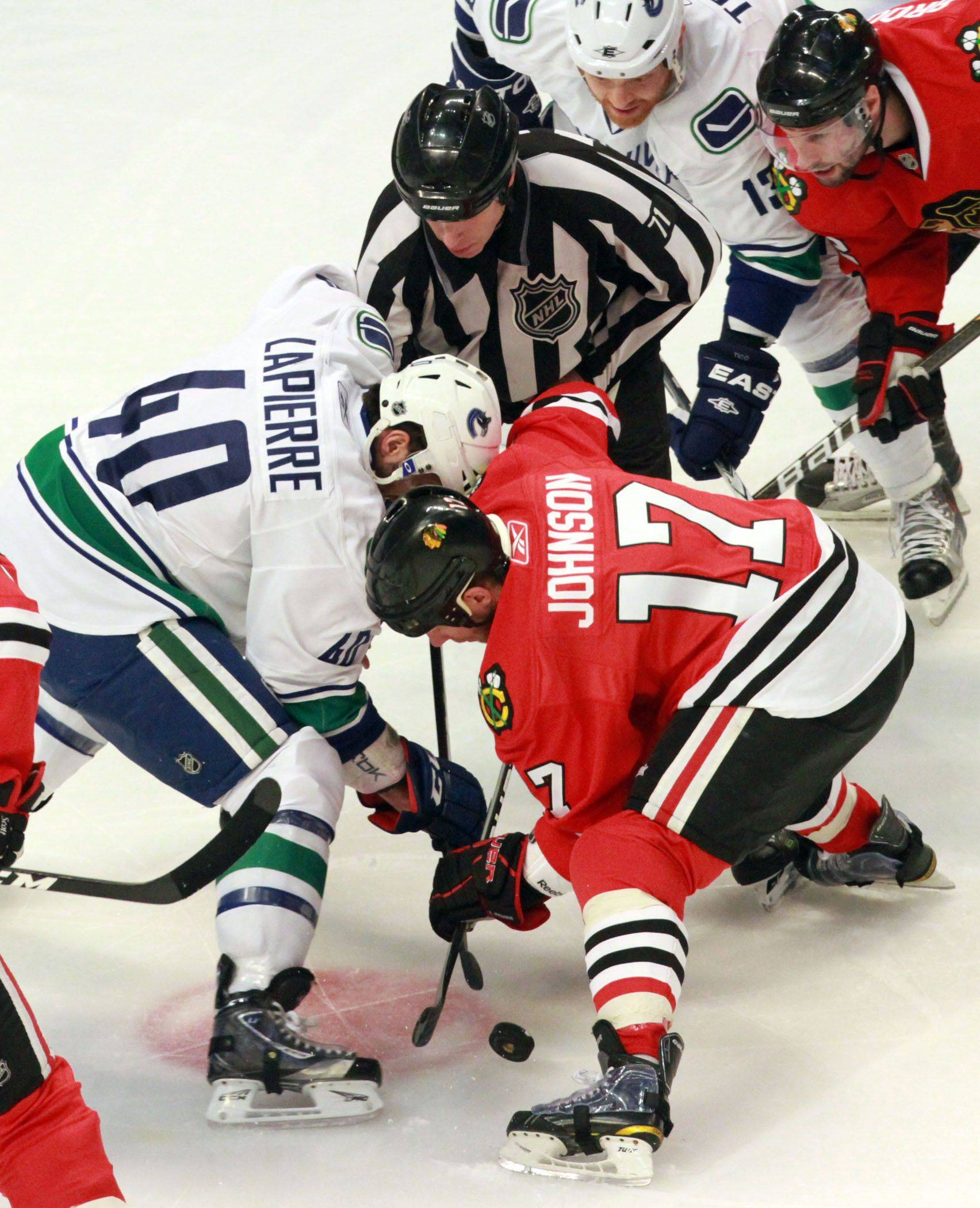 George LeClaire/gleclaire@dailyherald.com Chicago Blackhawks' Ryan Johnson in a face off with Vancouver Canucks' Maxium Lapierre in game 6 of the Stanley Cup quarterfinals at the United Center in Chicago on Sunday.
