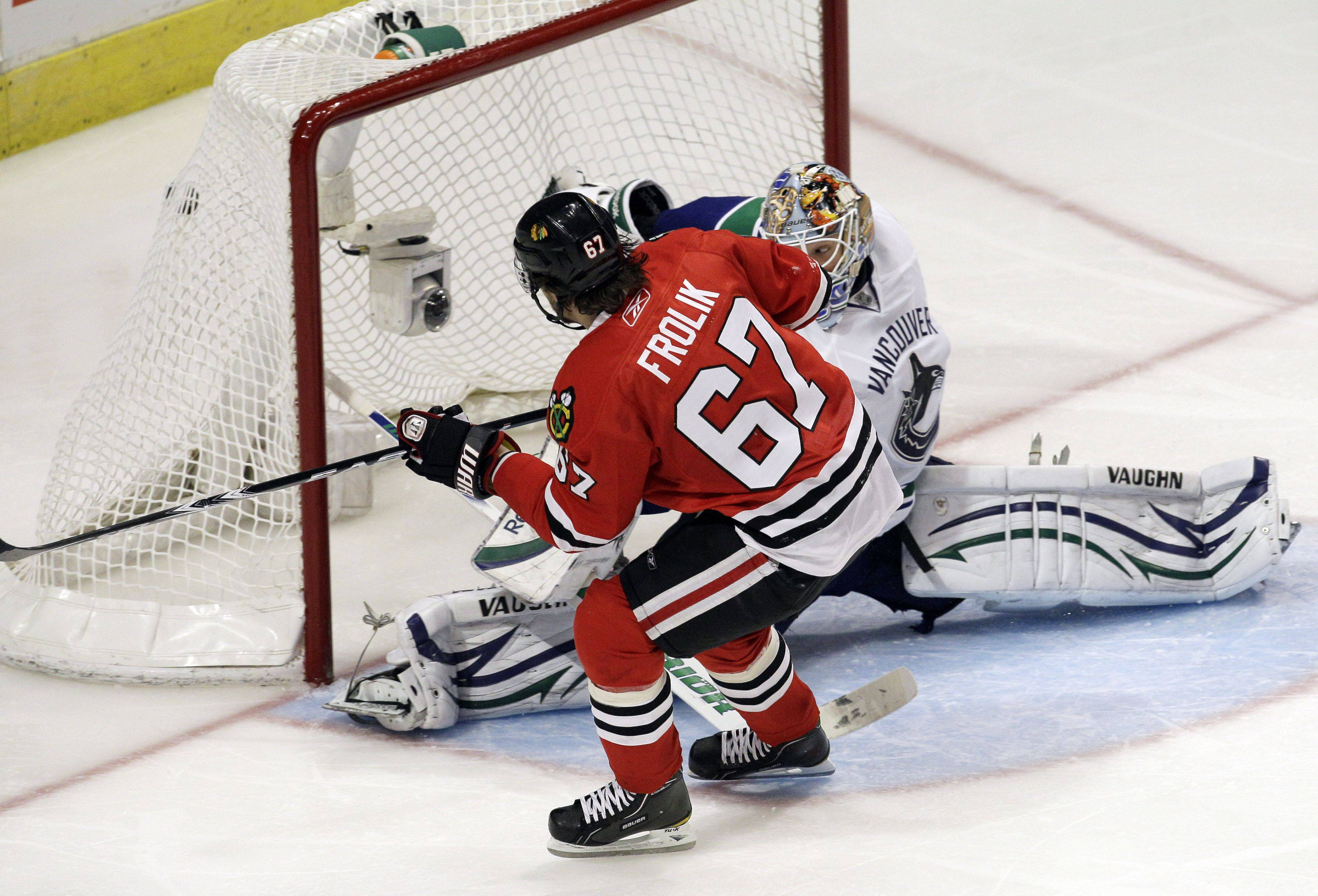 "Michael Frolik scores a goal on a penalty shot against Cory Schneider during the Hawks' Game 6 victory at the United Center. ""I think Fro is really coming into himself as a Blackhawk,"" said teammate Dave Bolland."