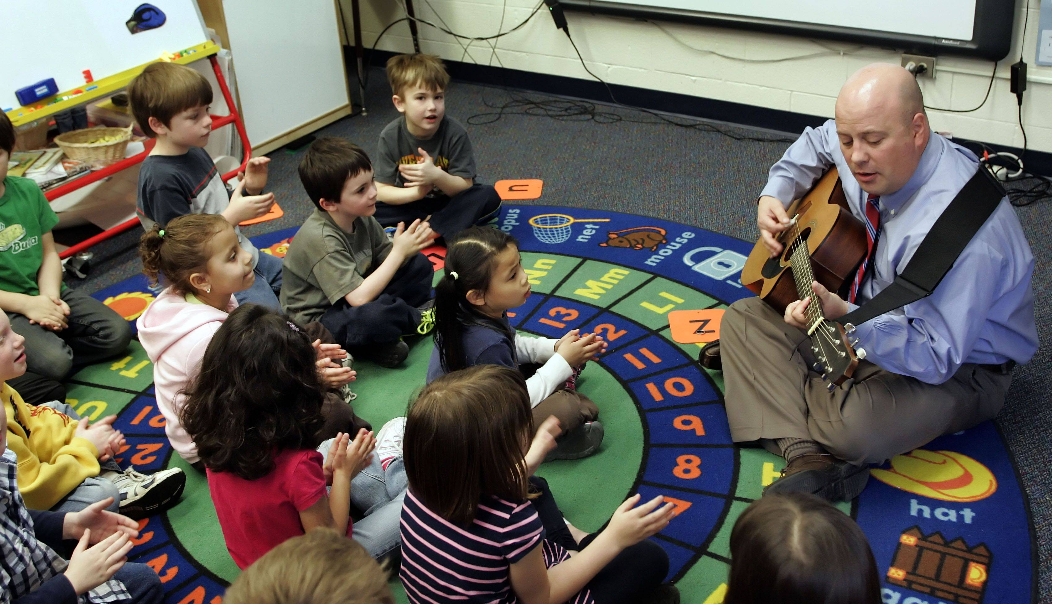 Adler Park School Principal Jon Bogie entertains the kindergarten class with his guitar in Libertyville. Bogie brings his love of music to the role of school principal.
