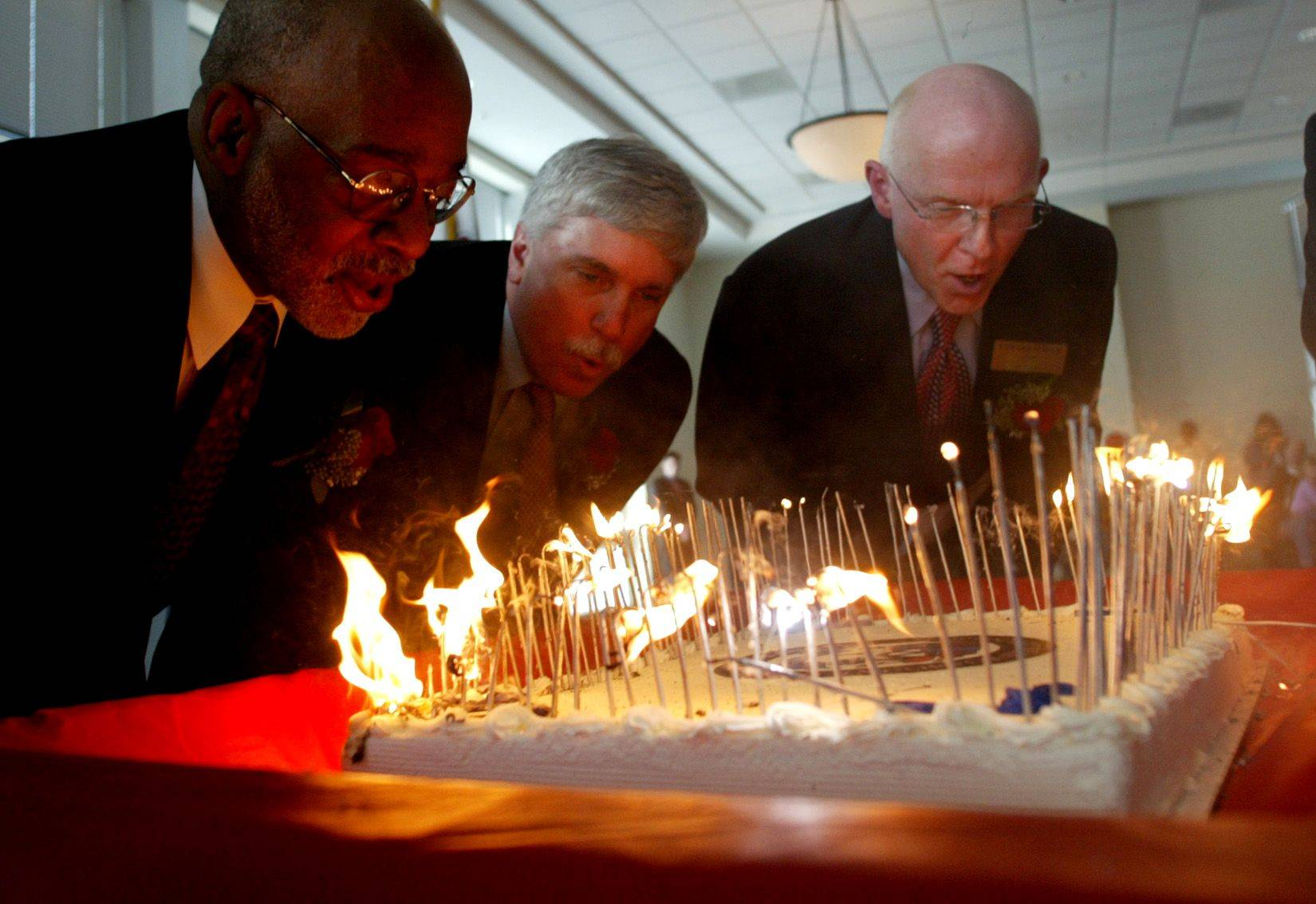 Elgin Mayor Ed Schock, far right, and Councilmen John Walters, center, and Robert Gilliam blow out the candles on Elgin's 150th birthday cake in 2004.