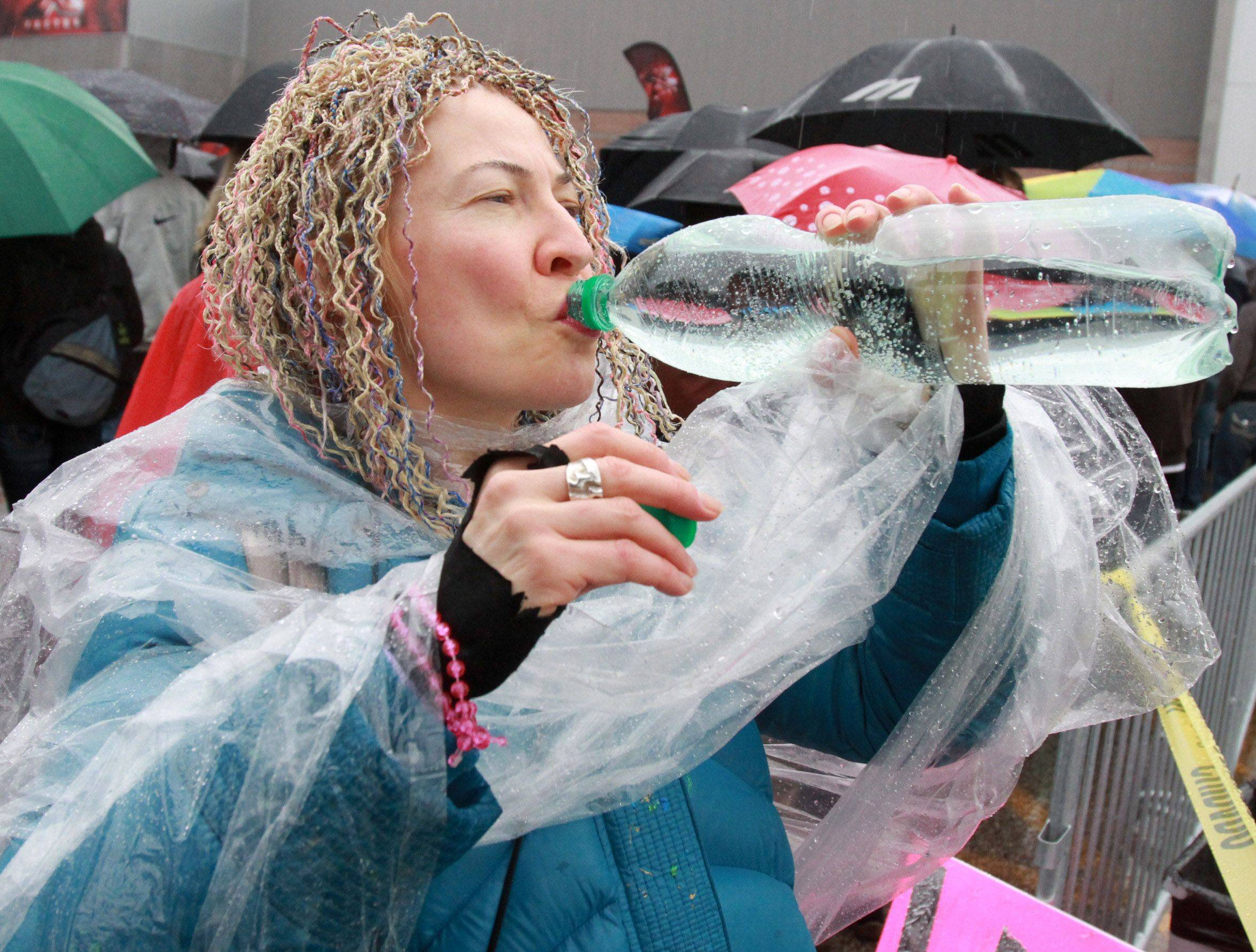 Lisa Janoschka a Hersey High School takes a drink of water before belting out her song in the parking lot of the Sears Centre Wednesday.