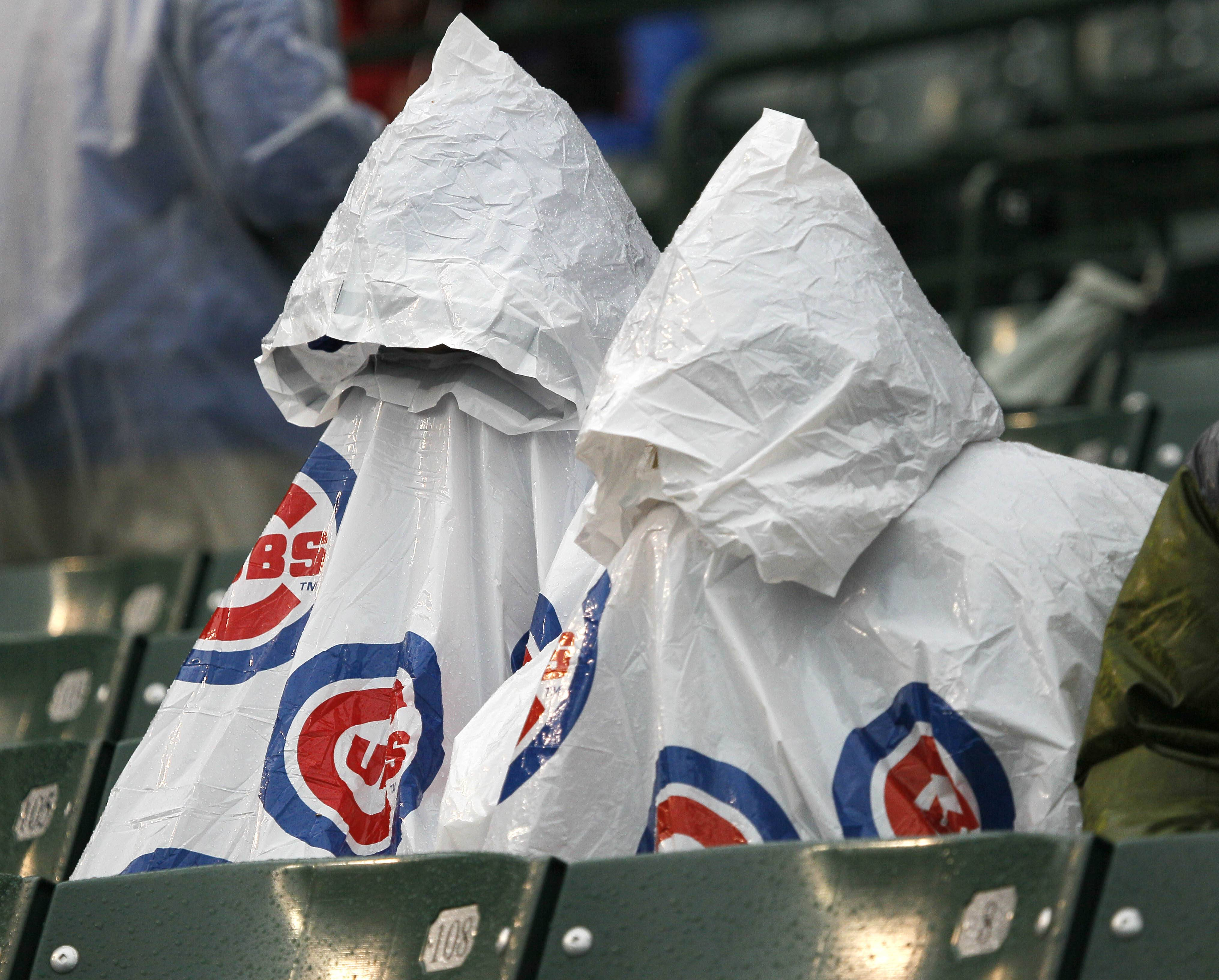 Cubs fans cover up during a rain delay Wednesday at Wrigley Field. The game is postponed due to rain and scheduled for June 27.
