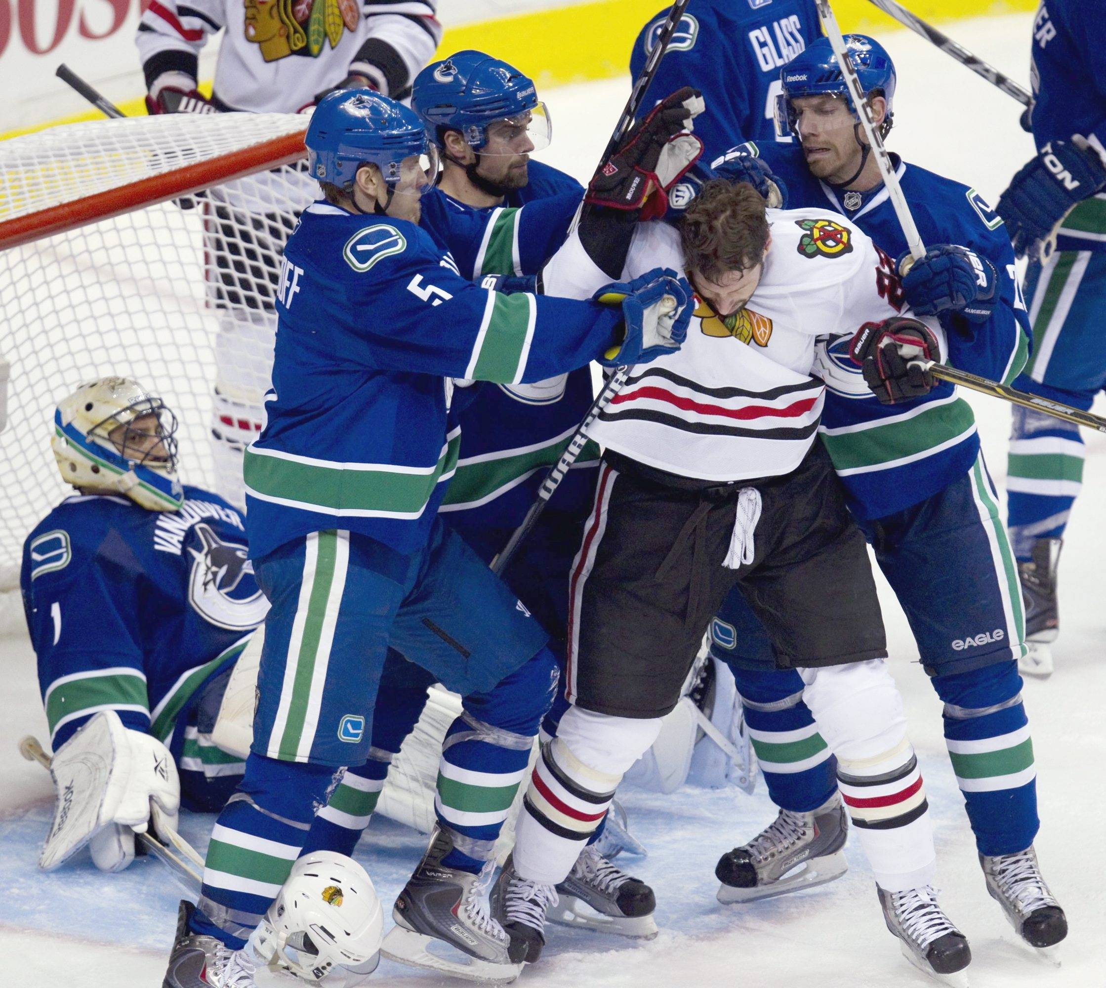 Canucks goaltender Roberto Luongo, left, looks on as teammates Christian Ehrhoff, of Germany; Dan Hamhuis; and Mikael Samuelsson, of Sweden, from second from left, try to clear Chicago Blackhawks' Troy Brouwer, center, from in front of their net during the second period of Game 7 of an NHL hockey Stanley Cup first-round playoff series in Vancouver, British Columbia, on Tuesday.