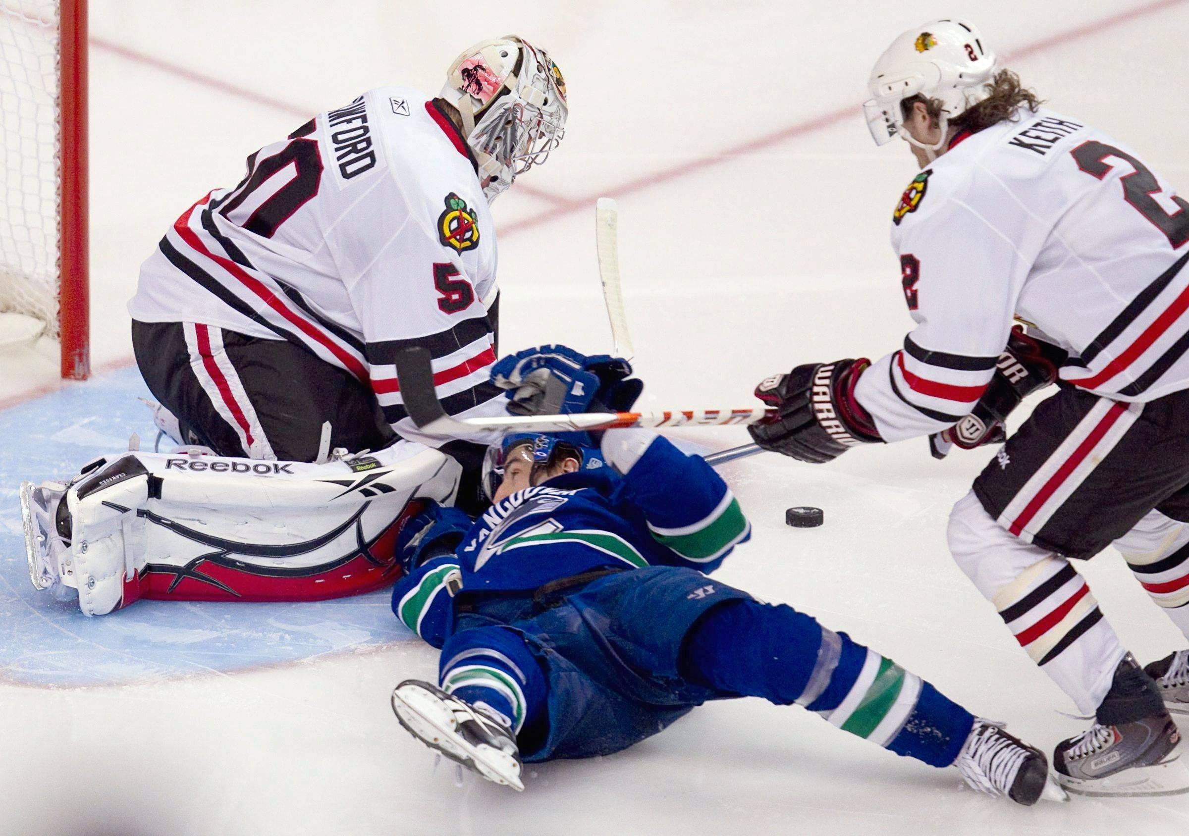 Vancouver Canucks' Alex Burrows slides into Chicago Blackhawks' goaltender Corey Crawford after being tripped by Chicago's Duncan Keith during the third period of game 7 of an NHL Western Conference quarterfinal Stanley Cup playoff hockey series in Vancouver, British Columbia Tuesday.