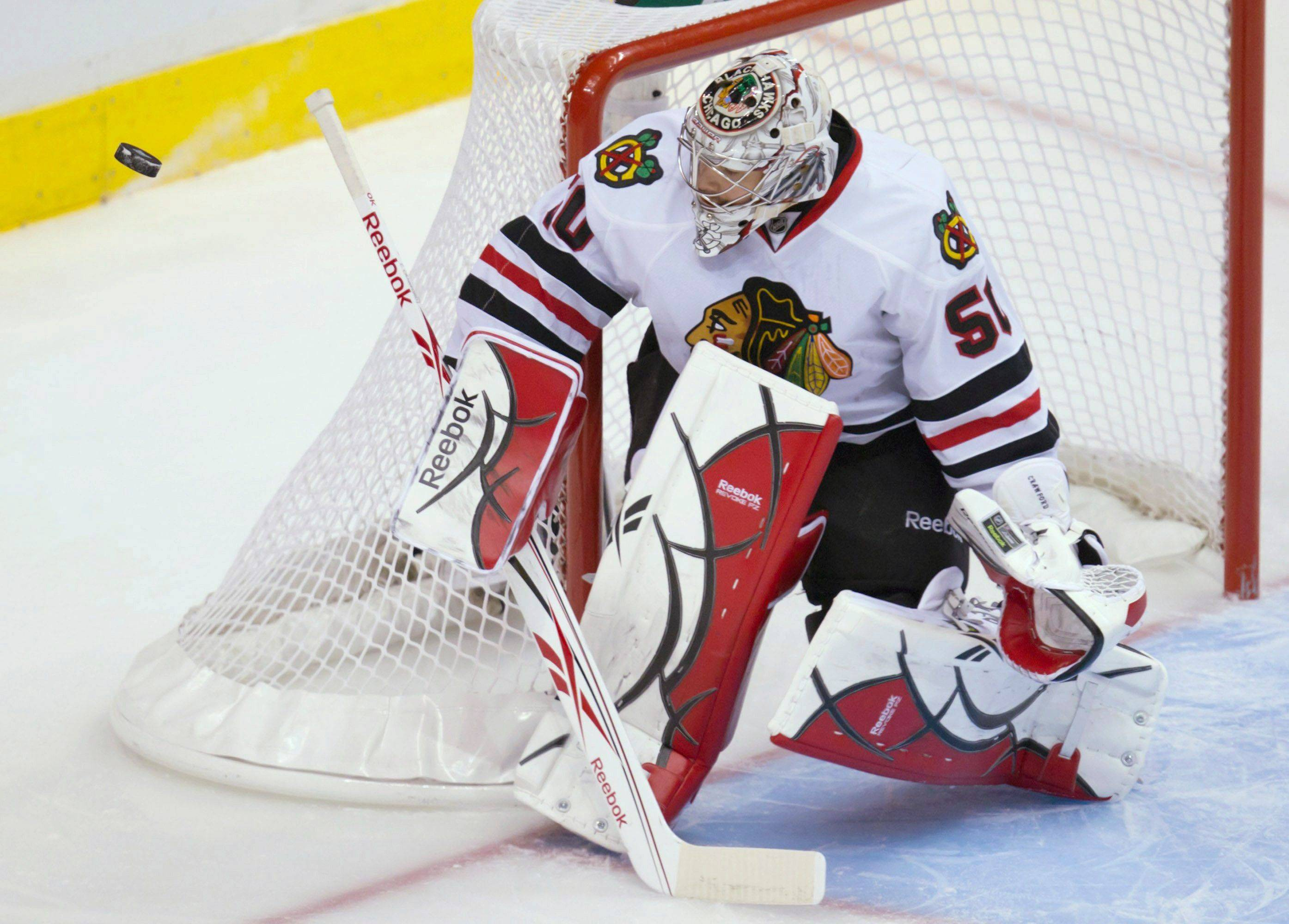 Blackhawks goalie Corey Crawford turns away a Vancouver Canucks shot during the first period of Game 7 Tuesday.