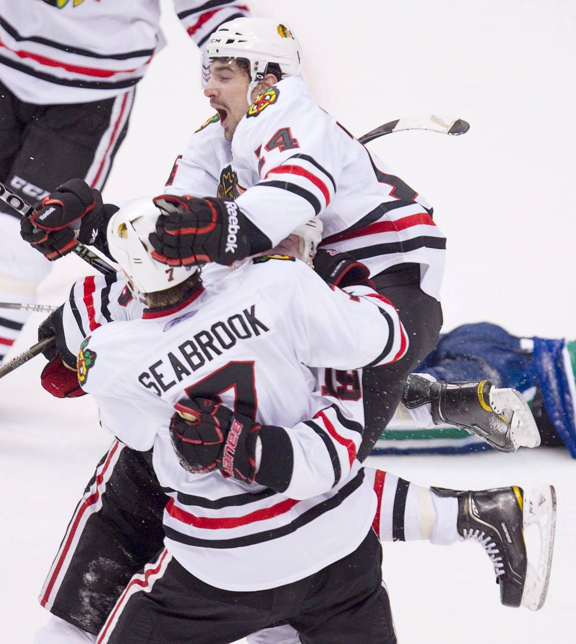 Chicago Blackhawks' Chris Campoli jumps on teammates Brent Seabrook and Jonathan Toews after Toews scored a game-tying goal against Vancouver with less than two minutes left in the third period Tuesday.