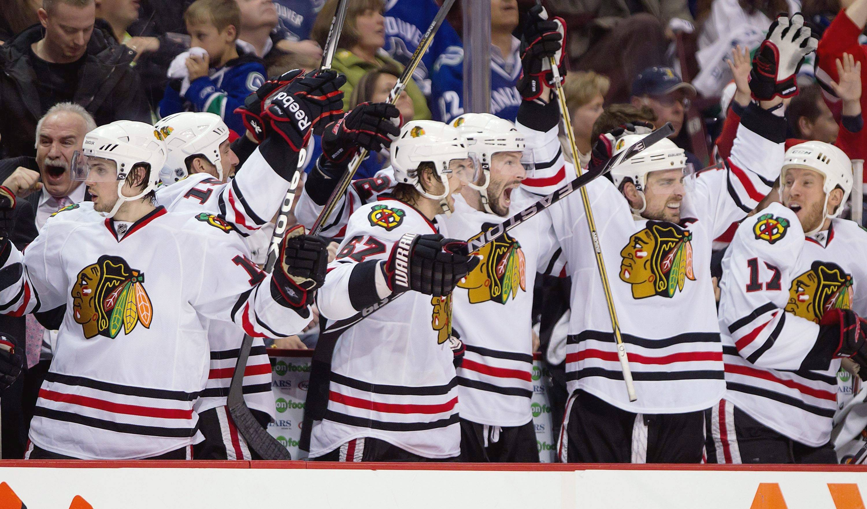 The Chicago Blackhawks bench celebrates after Jonathan Toews scored the game-tying goal against the Vancouver Canucks during the third period of game 7 of an NHL Western Conference quarterfinal Stanley Cup playoff hockey series Tuesday.