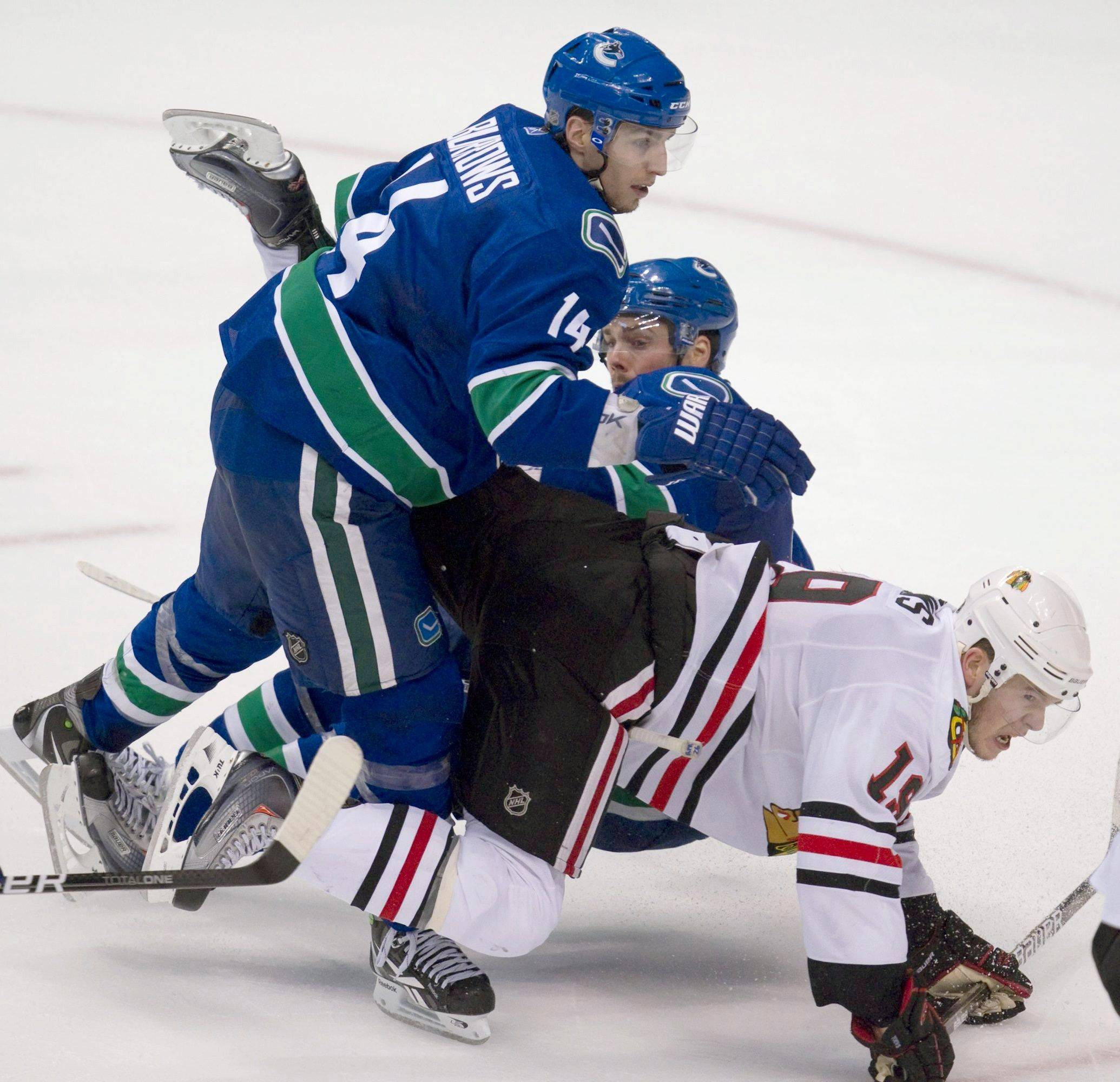 Vancouver Canucks' Alex Burrows, left, and teammate Dan Hamhuis take out Chicago Blackhawks' Jonathan Toews just before he scored during the third period of game 7.