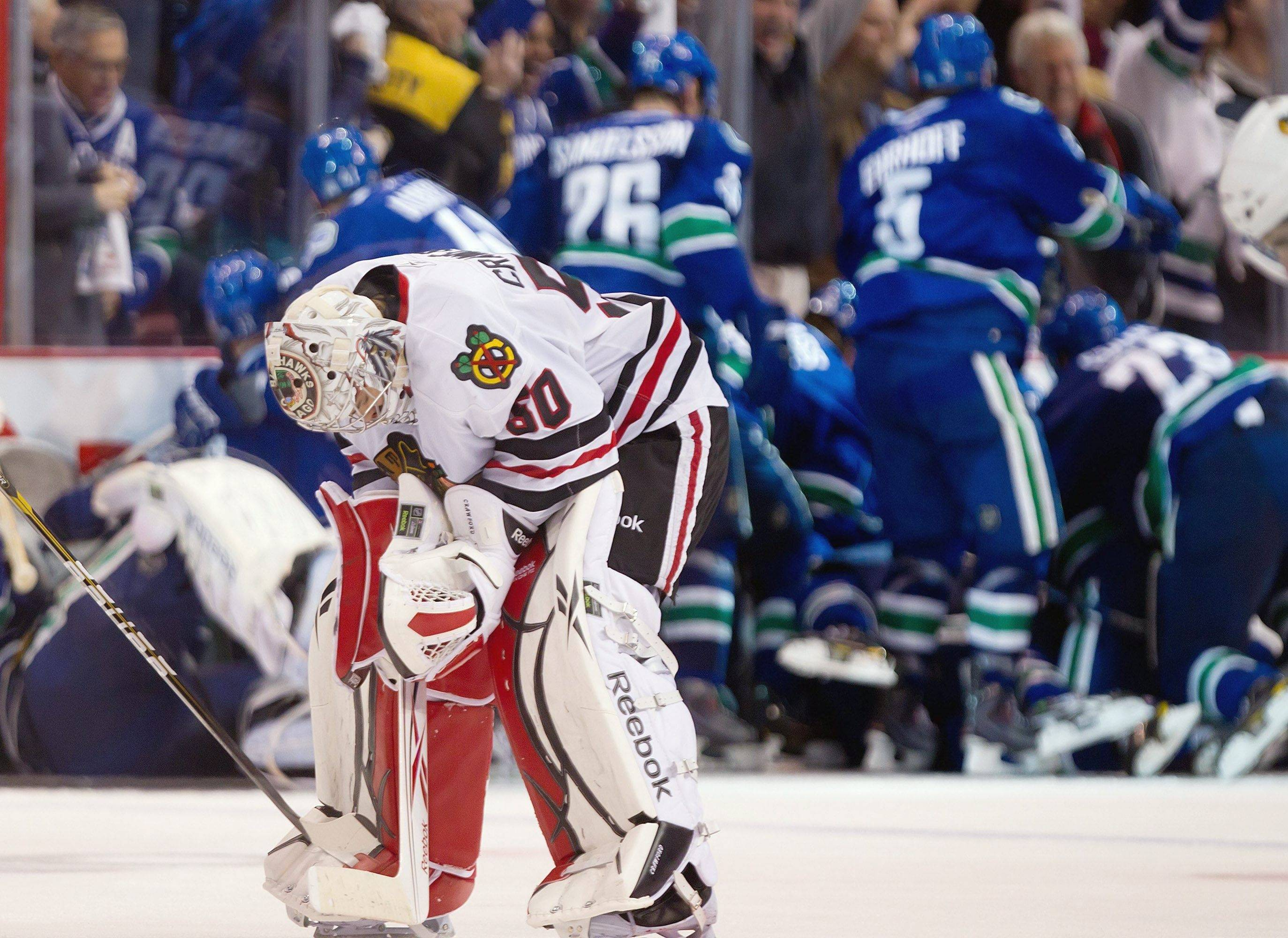 Chicago Blackhawks' Corey Crawford hangs his head as he leaves the ice as the Vancouver Canucks celebrate behind him after winning in overtime of game 7 of the NHL Western Conference quarterfinal Stanley Cup playoff series Tuesday, April 26, 2011.