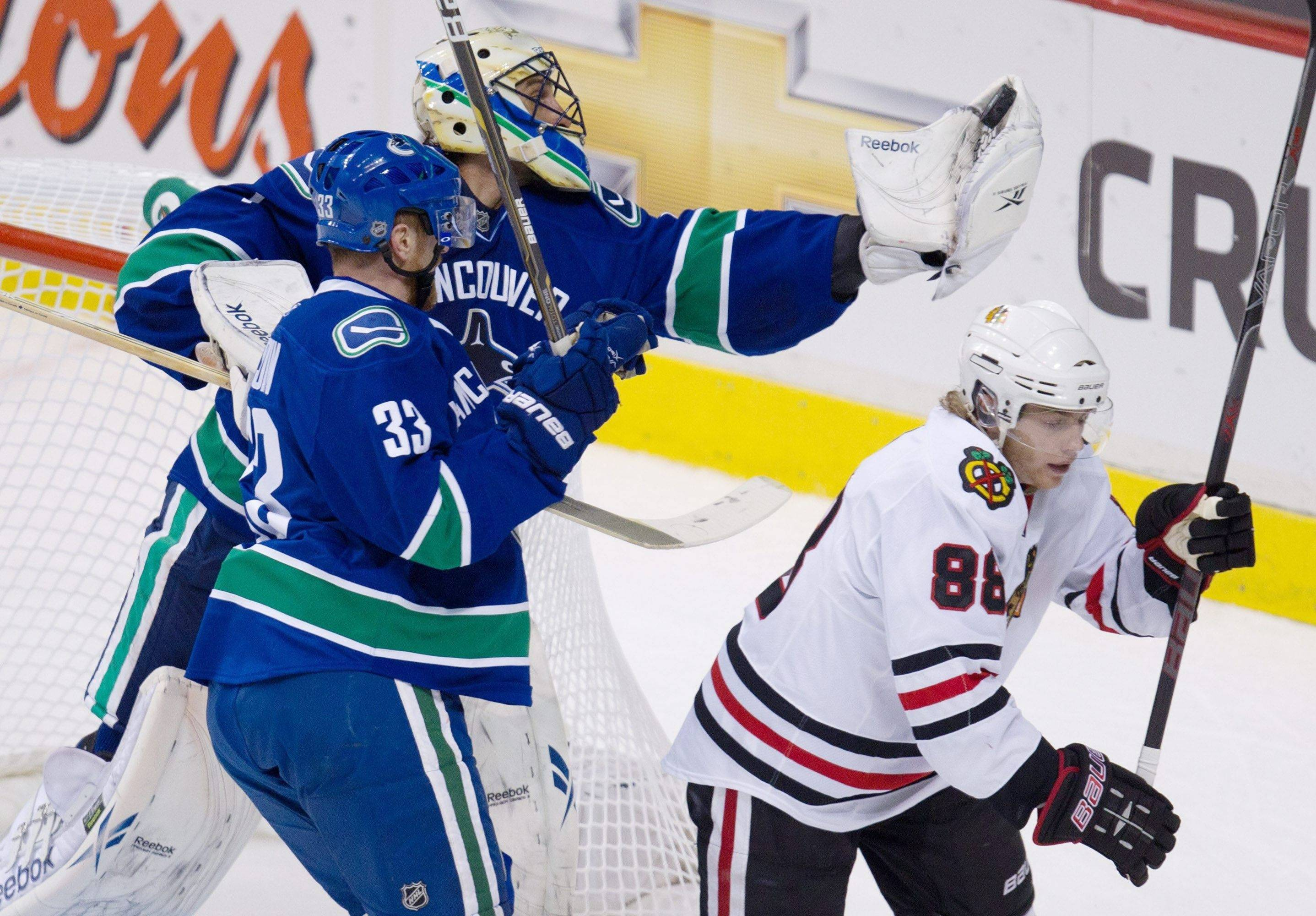 Vancouver Canucks' Roberto Luongo, top, gloves the puck as teammate Henrik Sedin and Chicago Blackhawks' Patrick Kane skate past during the first period Tuesday.