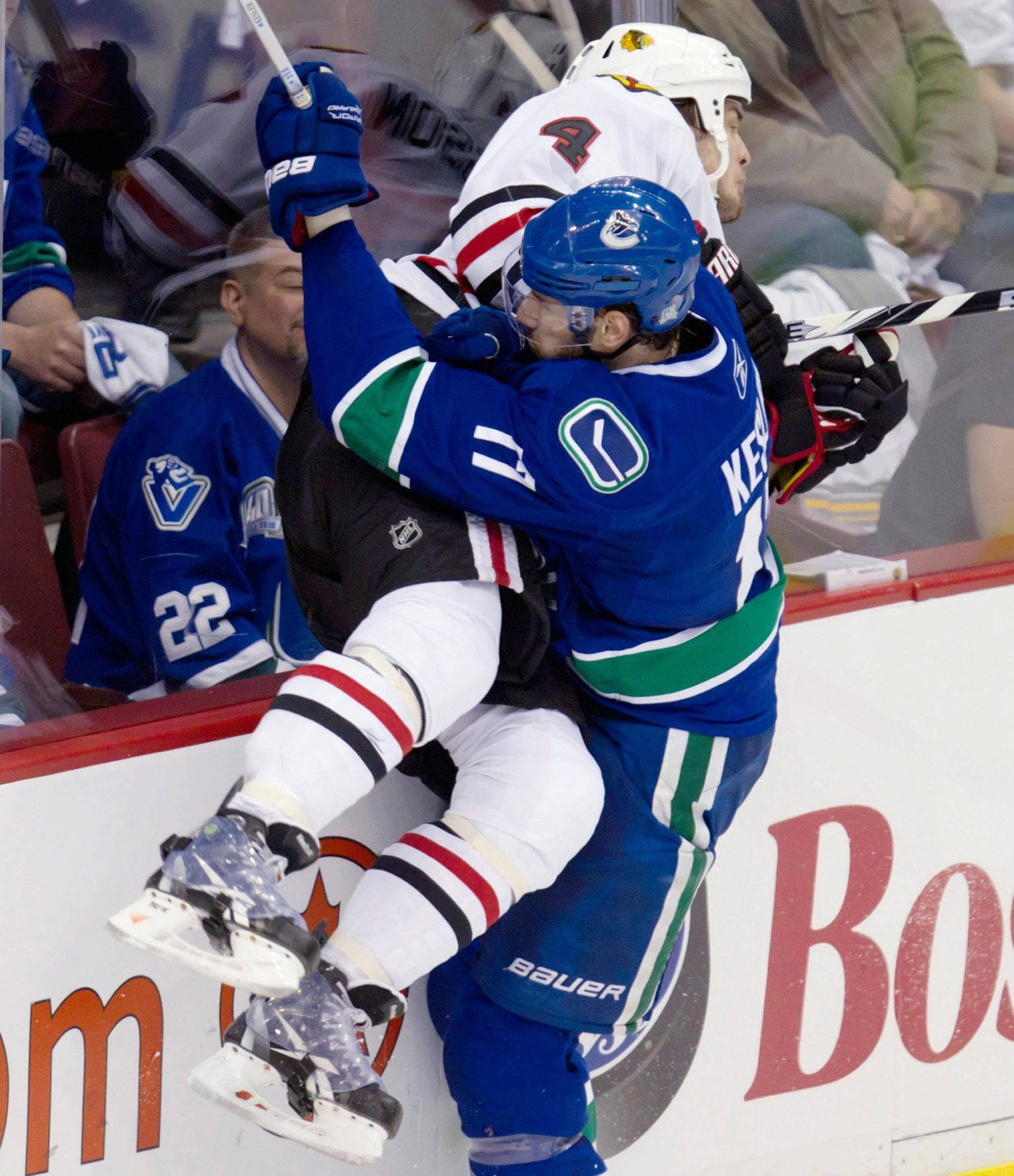 Vancouver Canucks' Ryan Kesler checks Chicago Blackhawks' Niklas Hjalmarsson during the first period of Game 7 of an NHL hockey Stanley Cup first-round playoff series Tuesday.