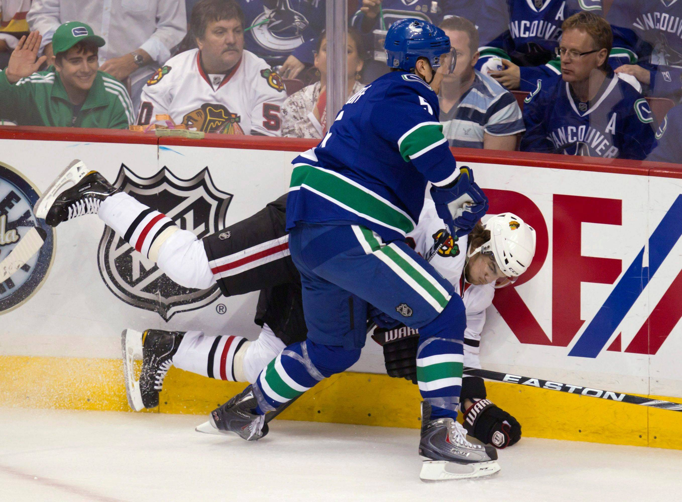 Vancouver Canucks' Christian Ehrhoff checks Chicago's Michael Frolik during Game 7.