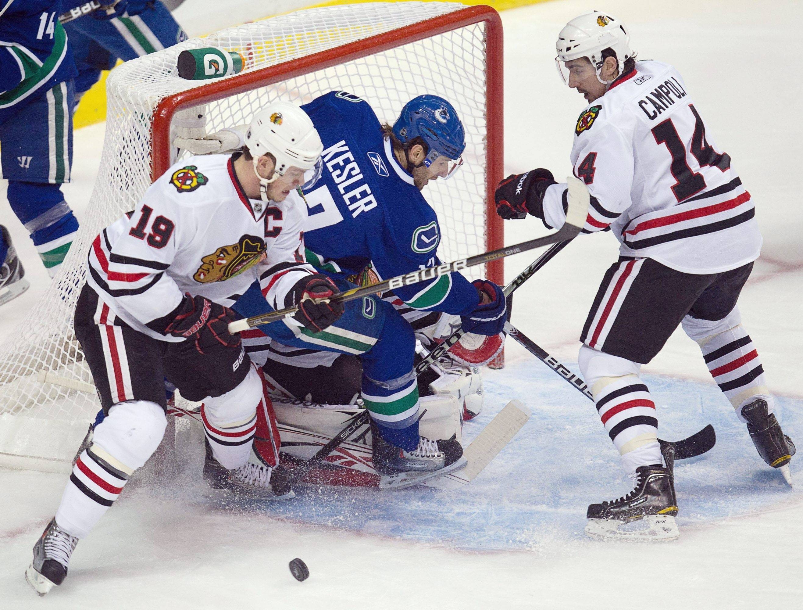Vancouver Canucks' Ryan Kesler is stopped by Chicago Blackhawks goalie Corey Crawford as Jonathan Toews, left, and Chris Campoli defend during the first period Tuesday.