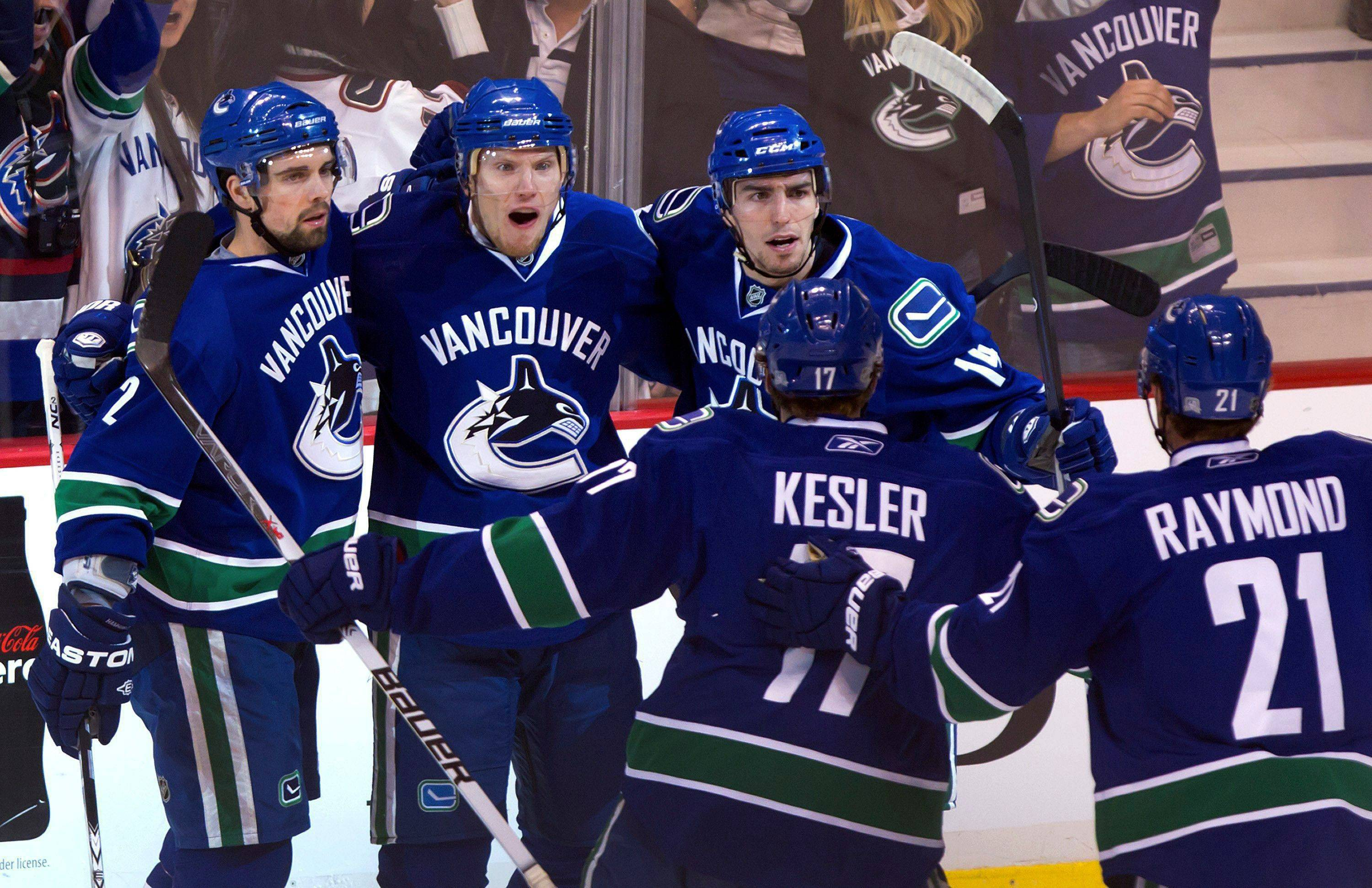 Vancouver Canucks' Dan Hamhuis, Christian Ehrhoff, Alex Burrows, Ryan Kesler and Mason Raymond celebrate Burrows' goal against the Chicago Blackhawks during the first period of Game 7 Tuesday.
