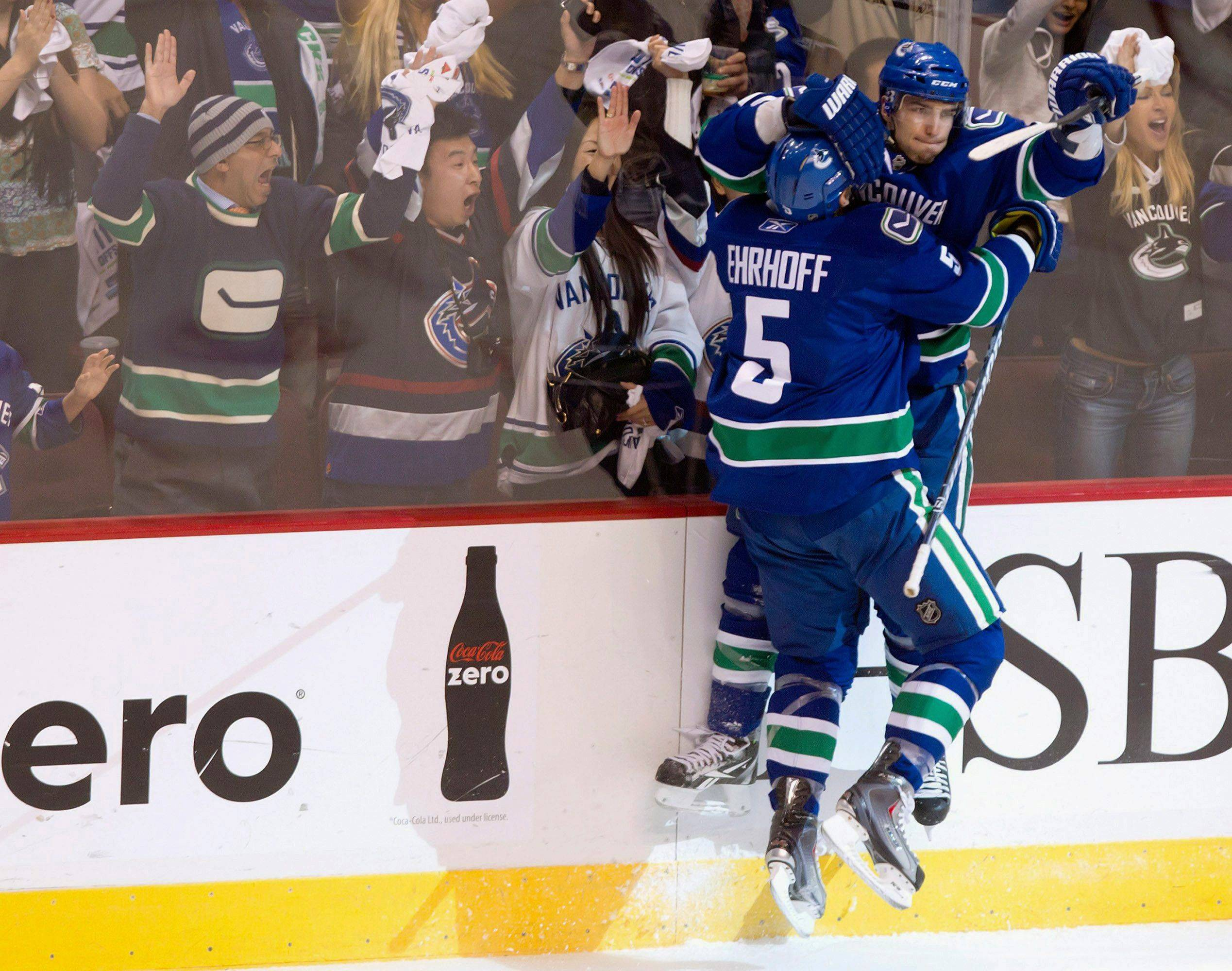 Vancouver Canucks' Christian Ehrhoff, left, and Alex Burrows celebrate Burrows' goal against the Blackhawks.