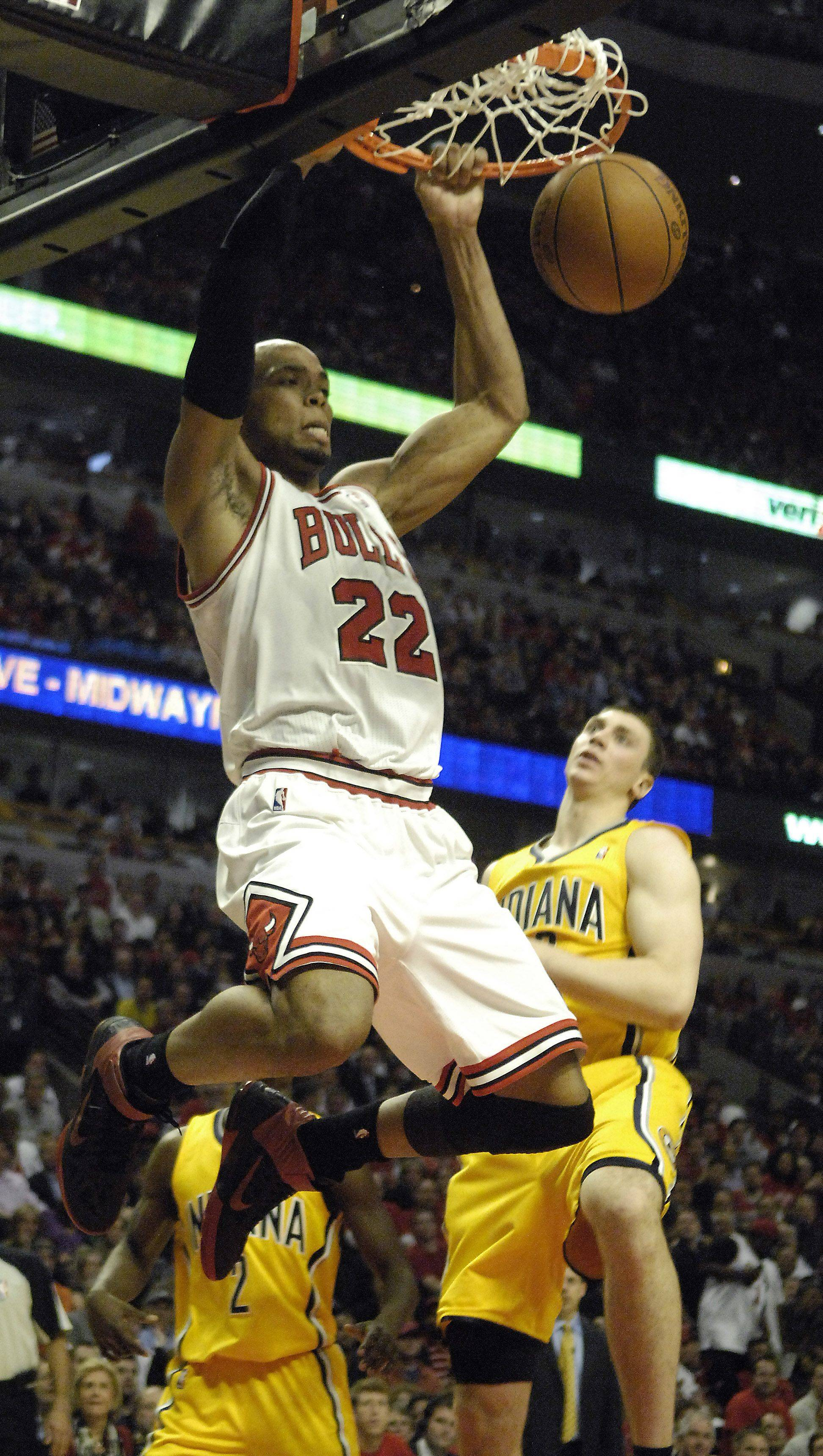 Taj Gibson throws down a dunk in front of Indiana Pacers' Tyler Hansbrough during game 5 in Chicago Tuesday.