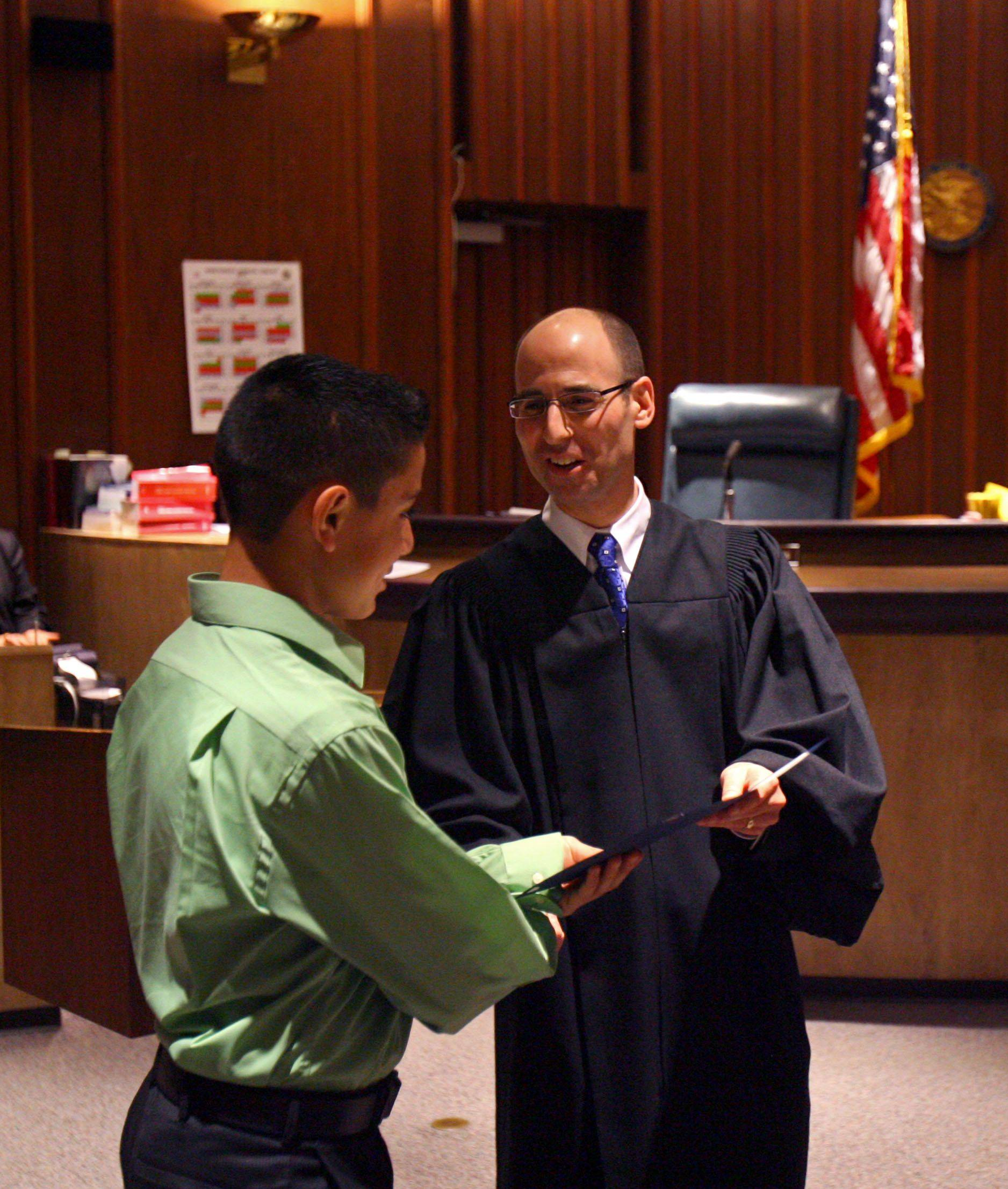 West Oak Middle School student Jose Gonzales receives a certificate of achievement from Judge Daniel B. Shanes at the Lake County Courthouse in Waukegan Friday. The ceremony was for kids who were successful in making better choices.