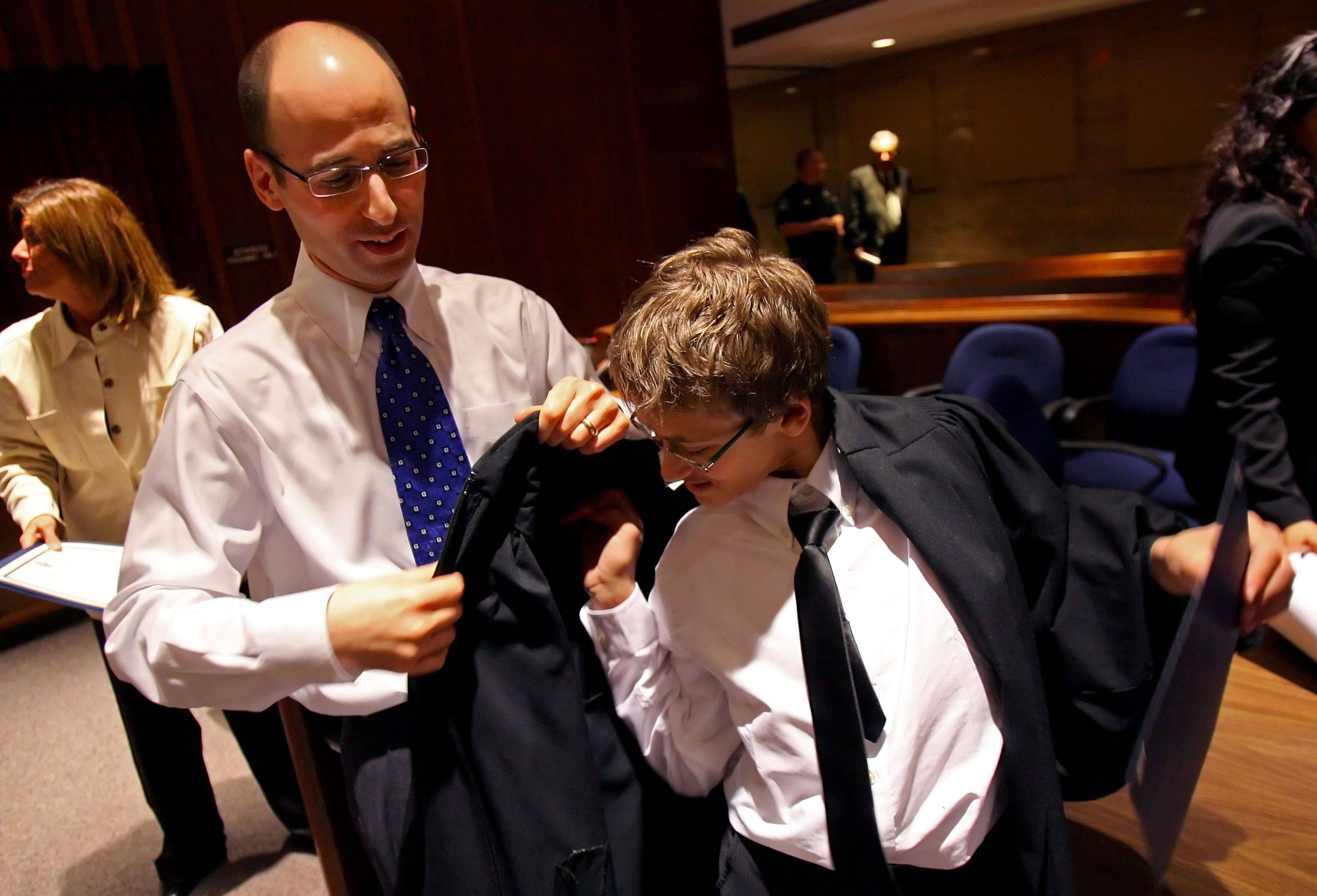 Judge Daniel B. Shanes helps Fremont Middle School eighth-grader Dennis Lind try on his robe as part of a recognition ceremony for kids who were successful in making better choices. Kids honored at the Lake County Courthouse were from Carl Sandburg, Fremont and West Oak middle schools.
